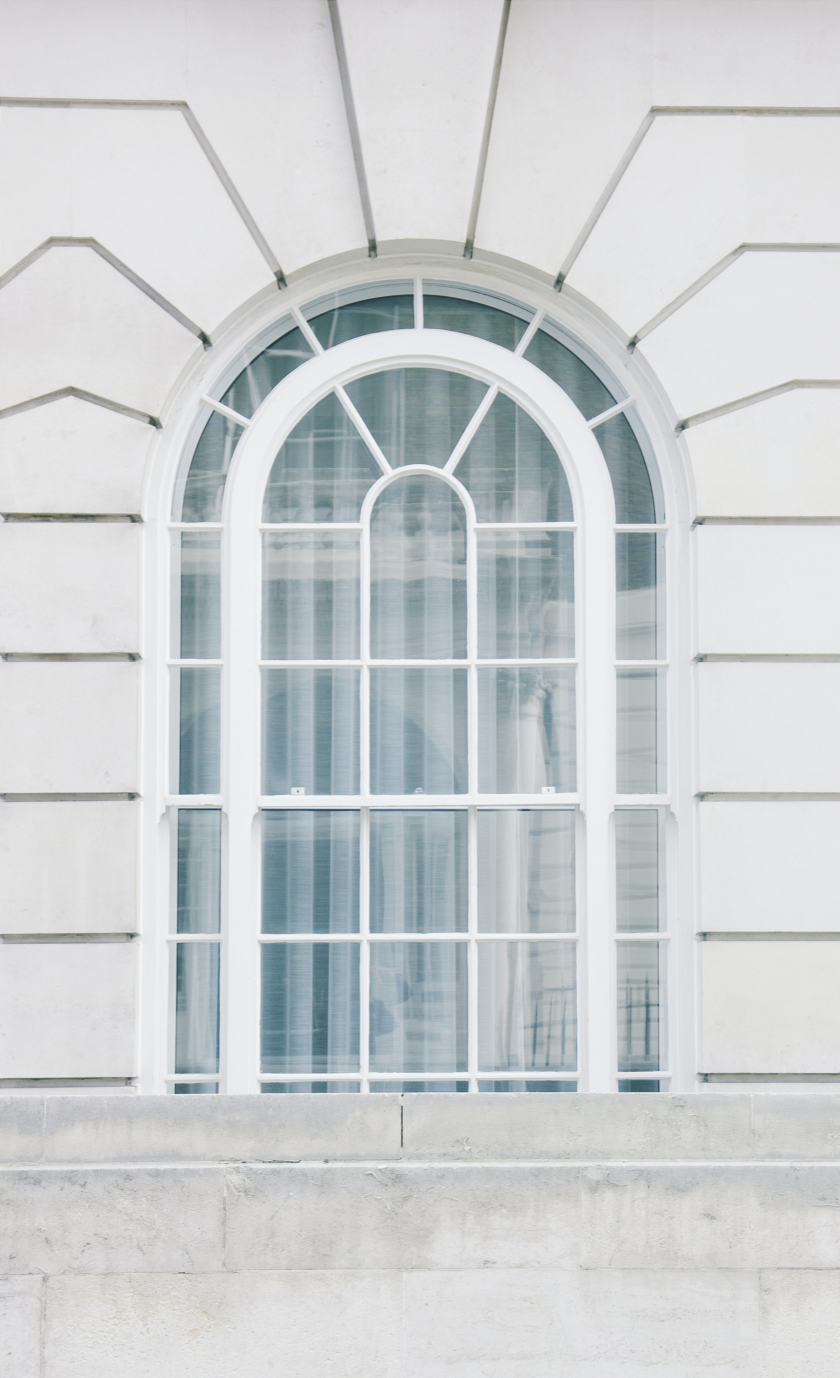 A white arched window in a building in London