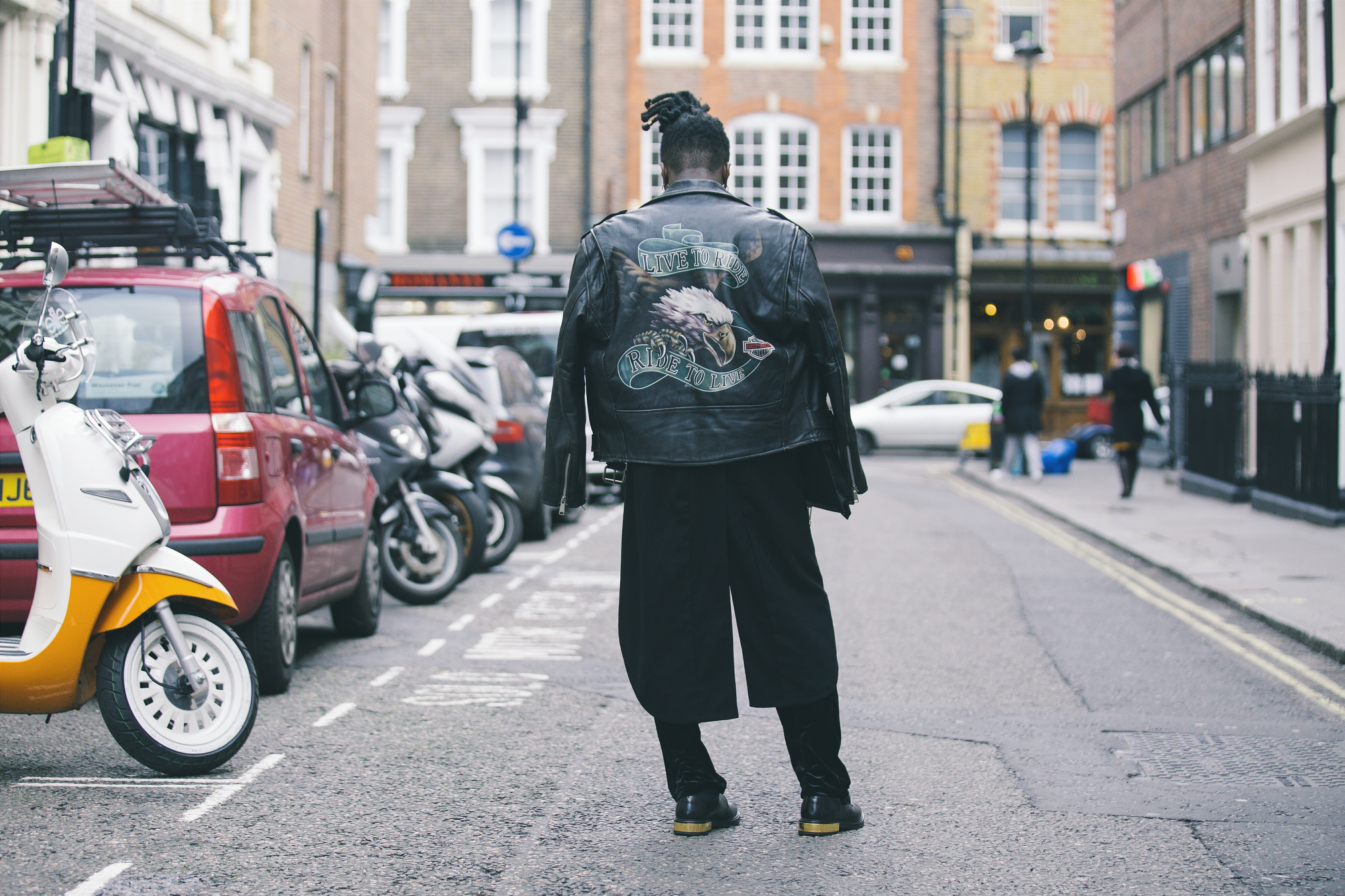 person wearing black jacket on road