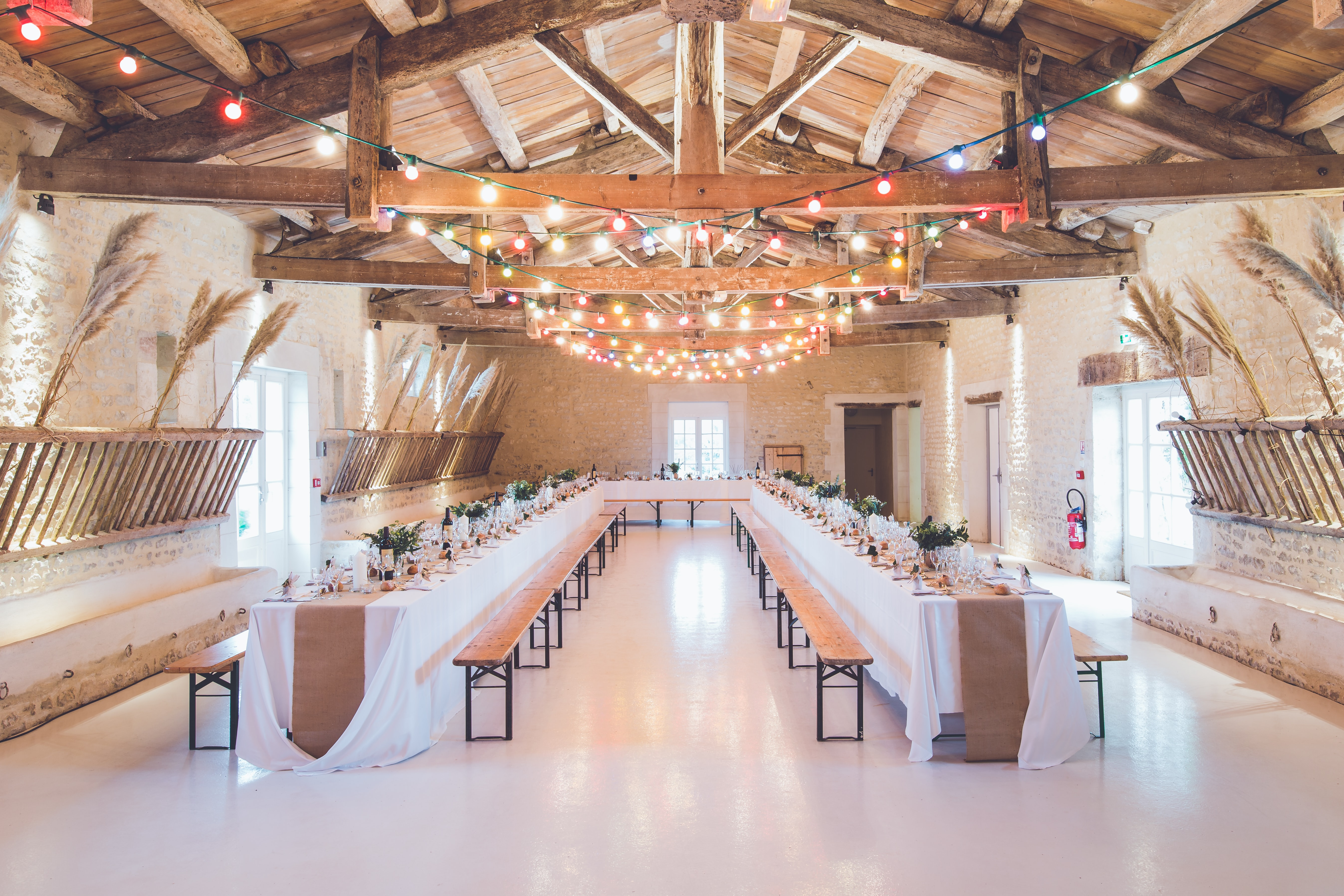 Wedding reception tables with wooden benches and string lights above them at Abbaye de la Grâce-Dieu