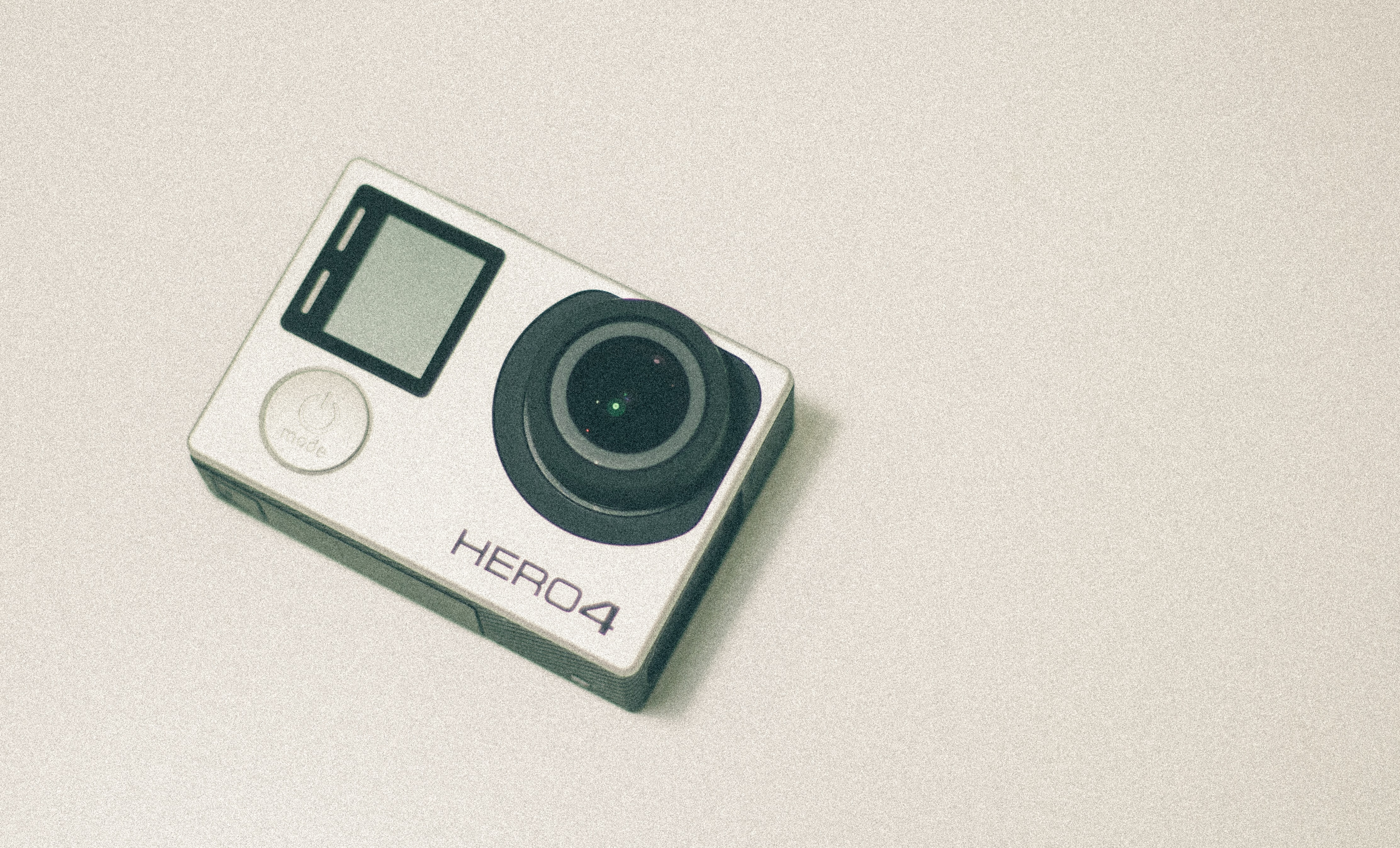 A GoPro Hero4 camera sitting on a white surface.