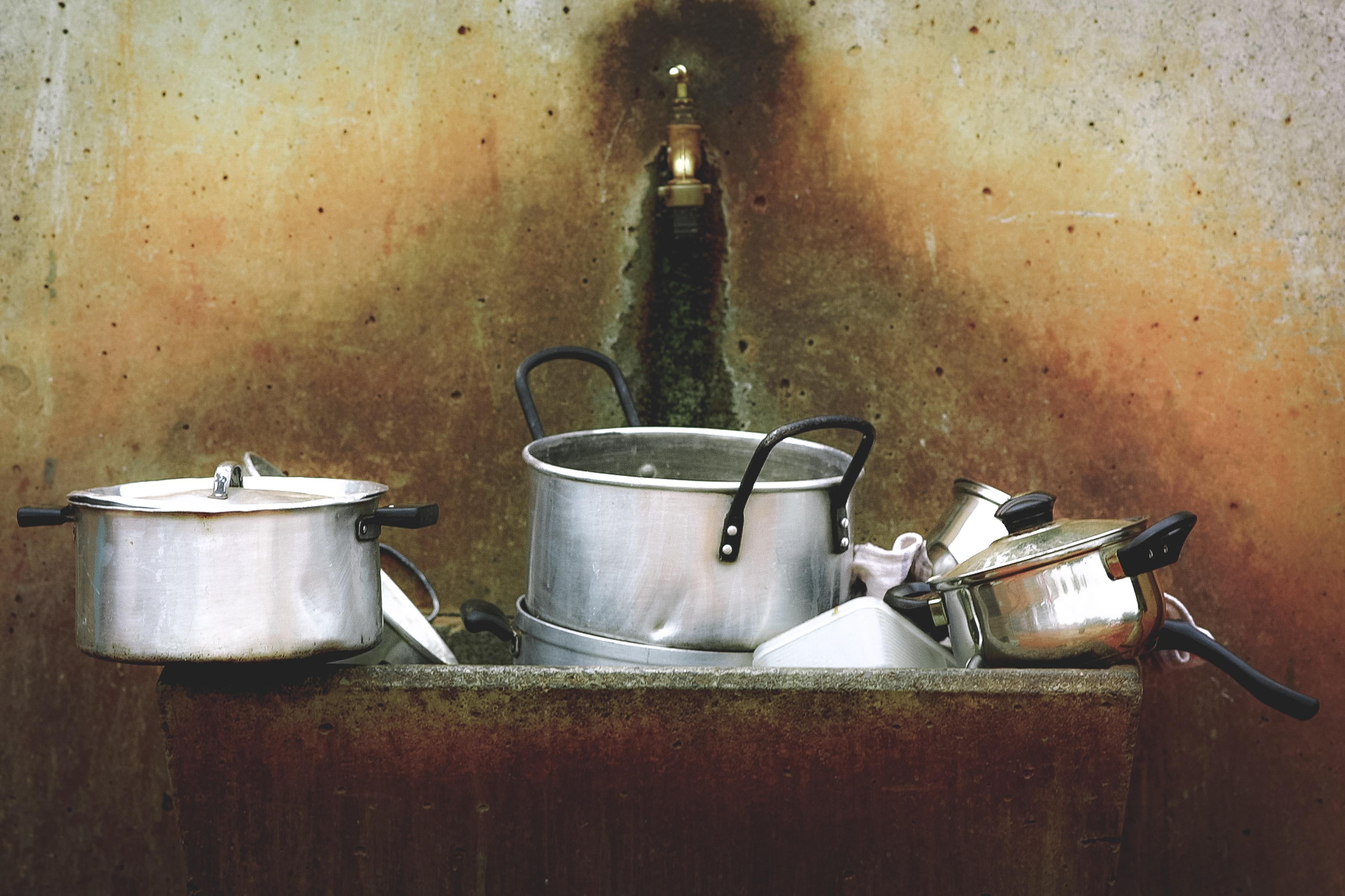 Silver pots and dishes in a dirty old sink with a small faucet