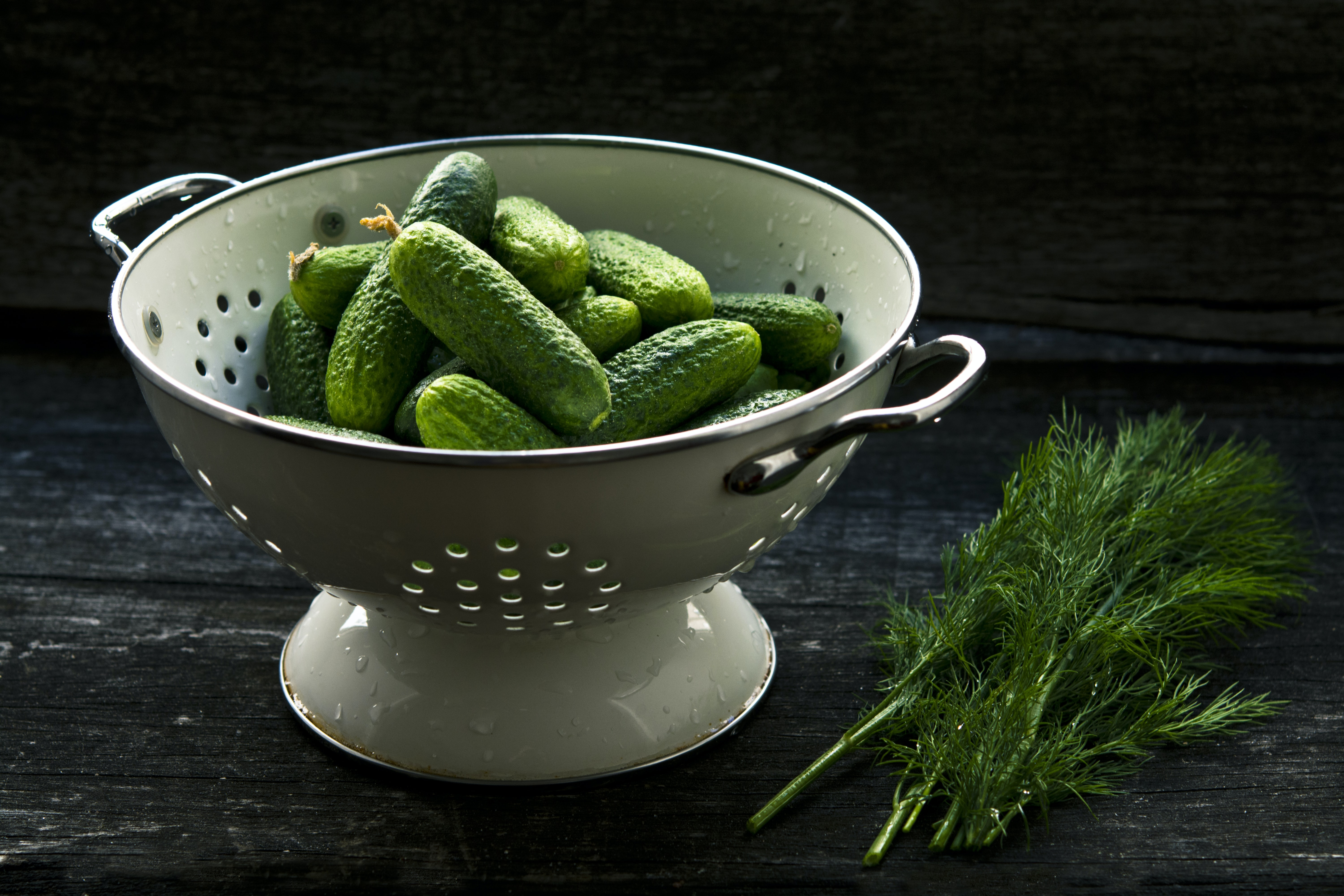 Colander with fresh cucumbers on a table next to dill and herbs