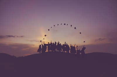 silhouette of people standing on hill graduation teams background