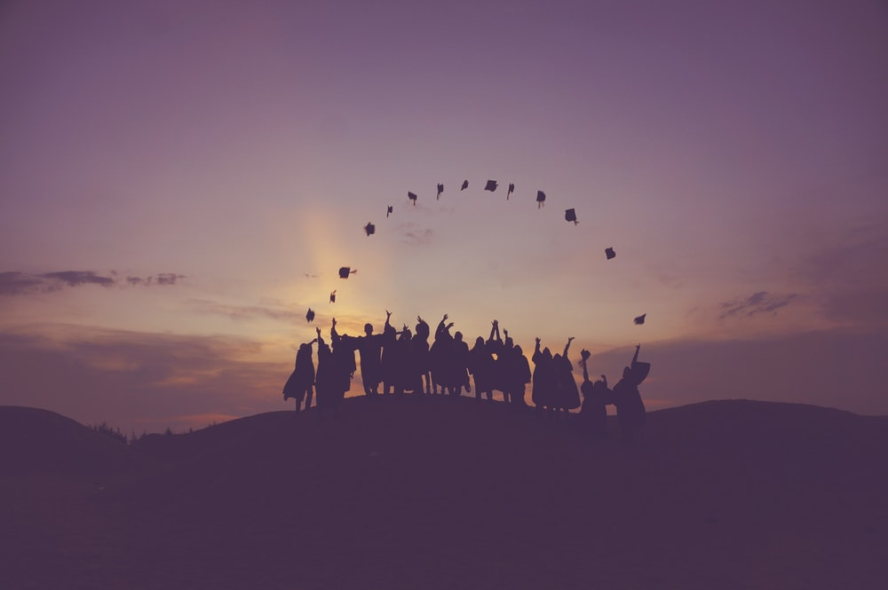 A group of graduates at sunset throwing up their caps in Malacca