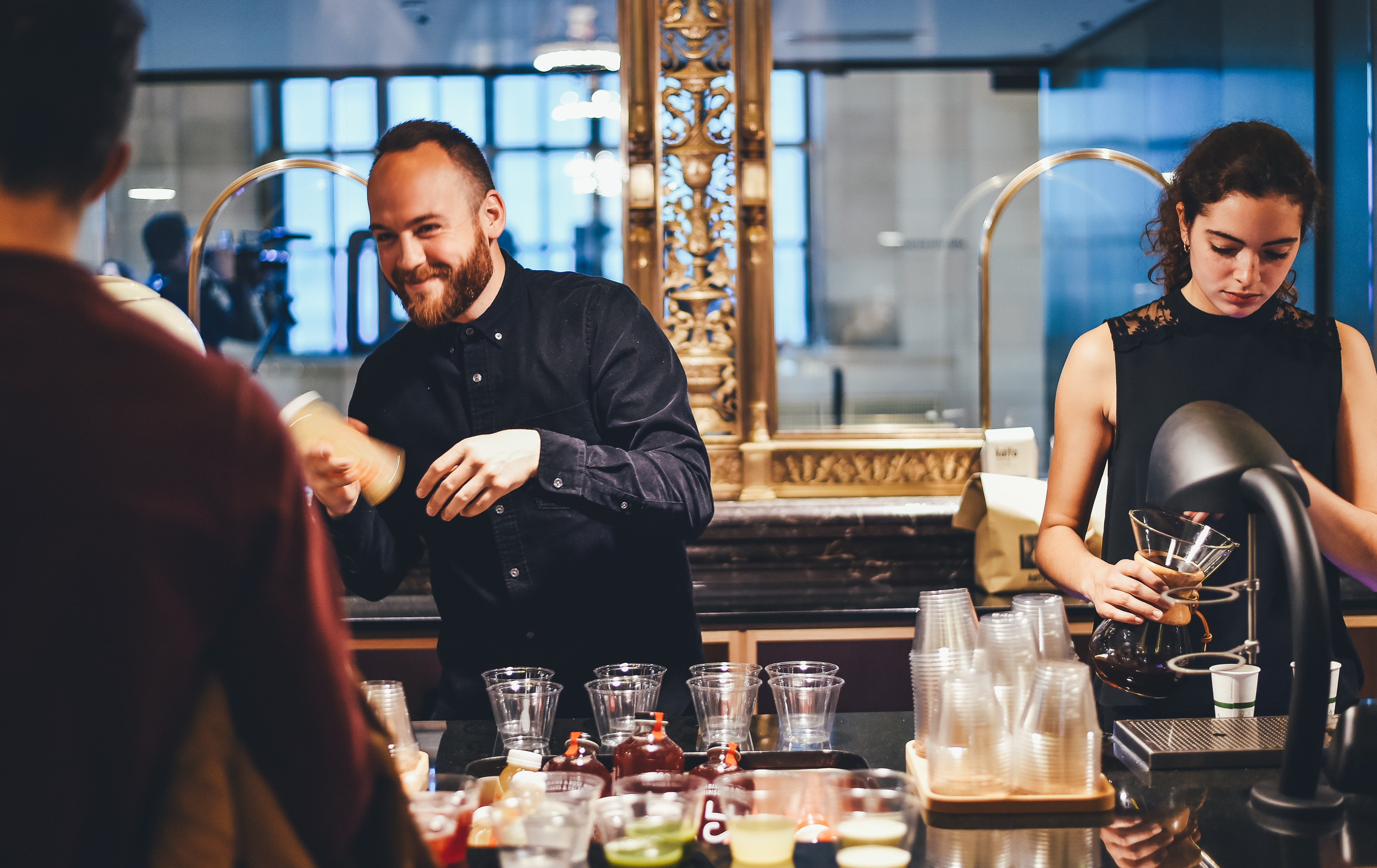Bartenders of different genders serving cocktail drinks in a bar