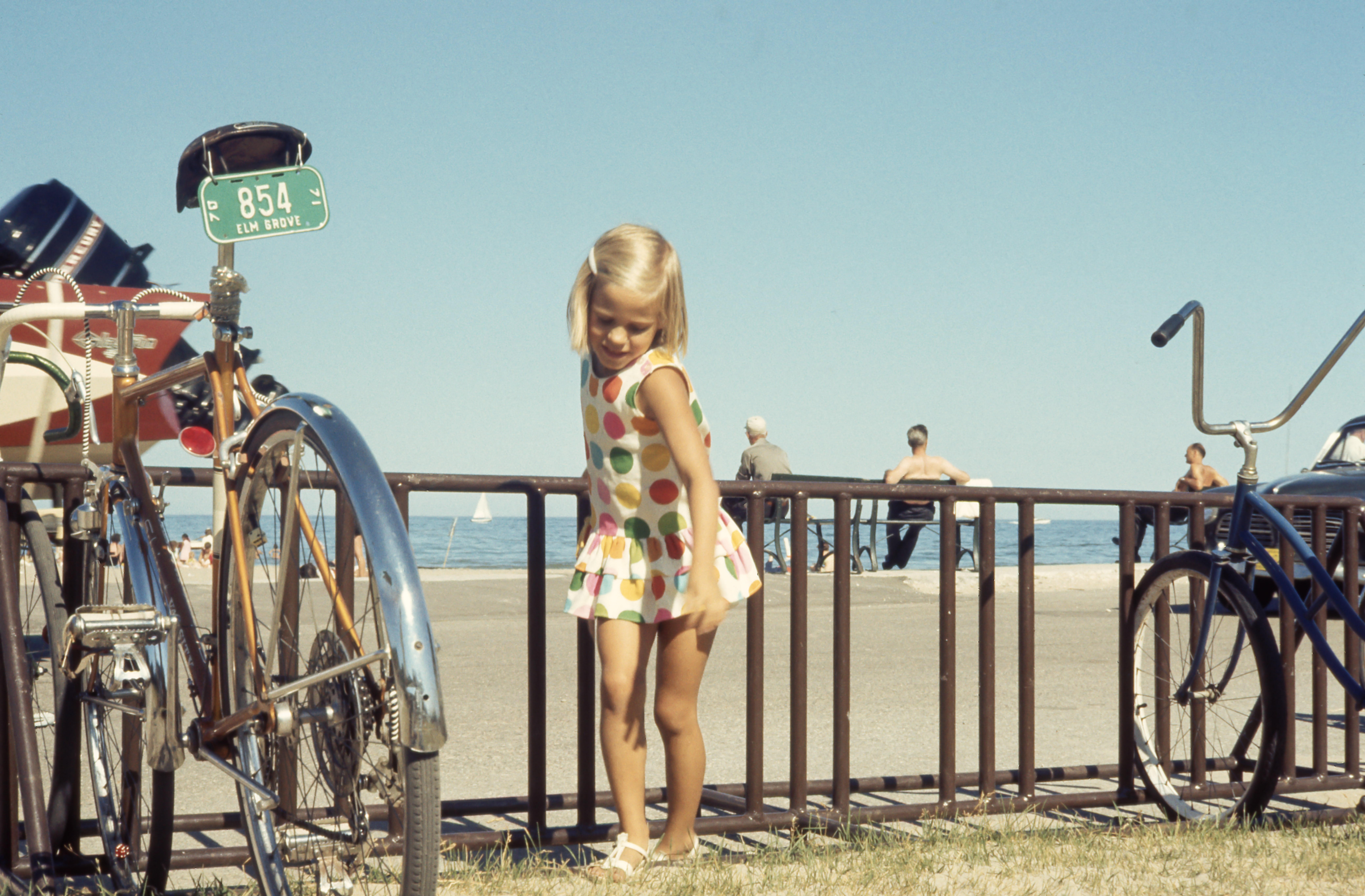Blonde kid girl poses for a shot beside bike while holding the railing in a summer day