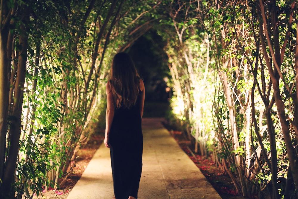 woman walking under green leaf trees