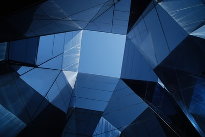 low angle photo of curtain wall building blue teams background