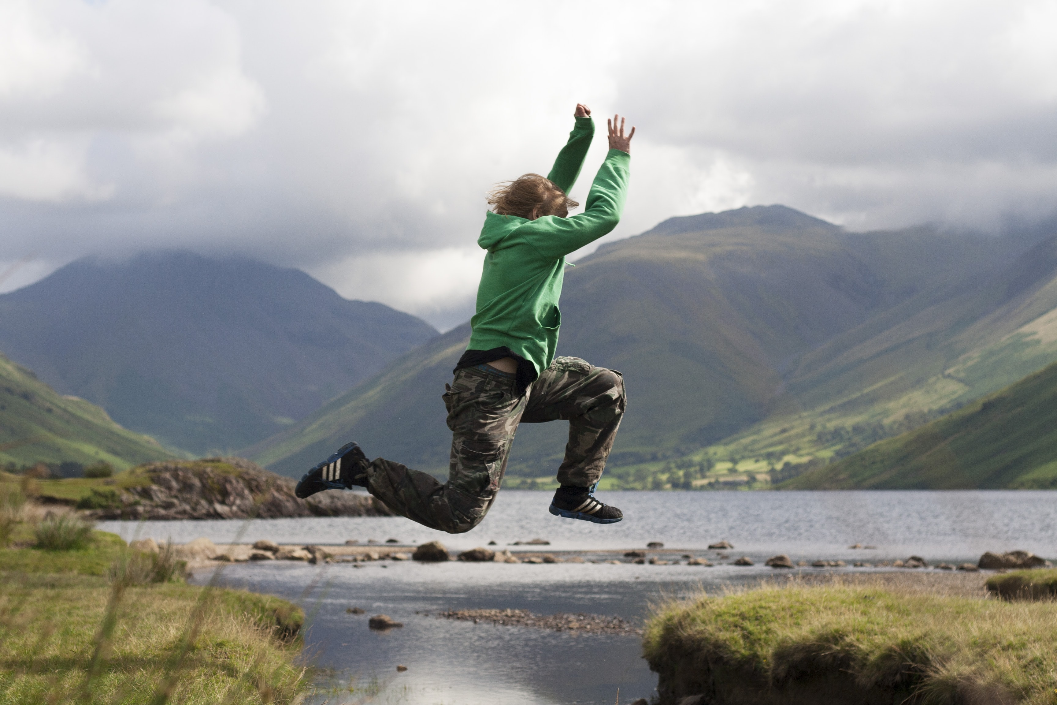 A person wearing camo pants and a green sweatshirt jumping by a lake and mountains in Scafell Pike
