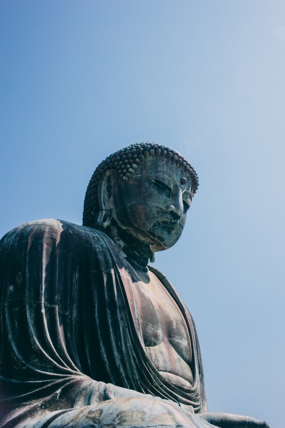 selective focus photography of Buddha statue during daytime