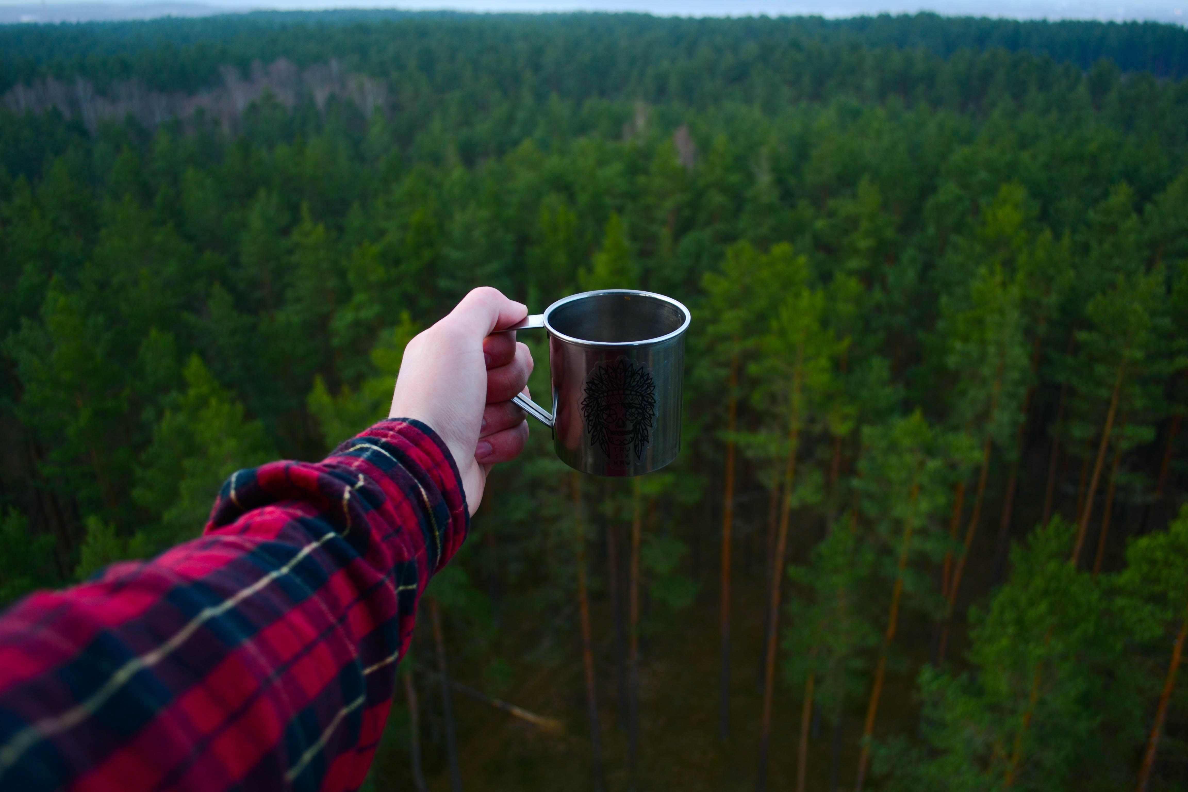 An outstretched arm of a person in a flannel shirt holding a mug with a view on a green forest