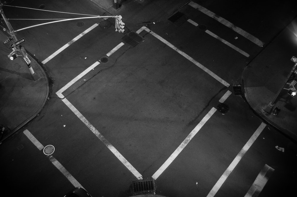 A look down at an empty intersection where traffic lines form a square