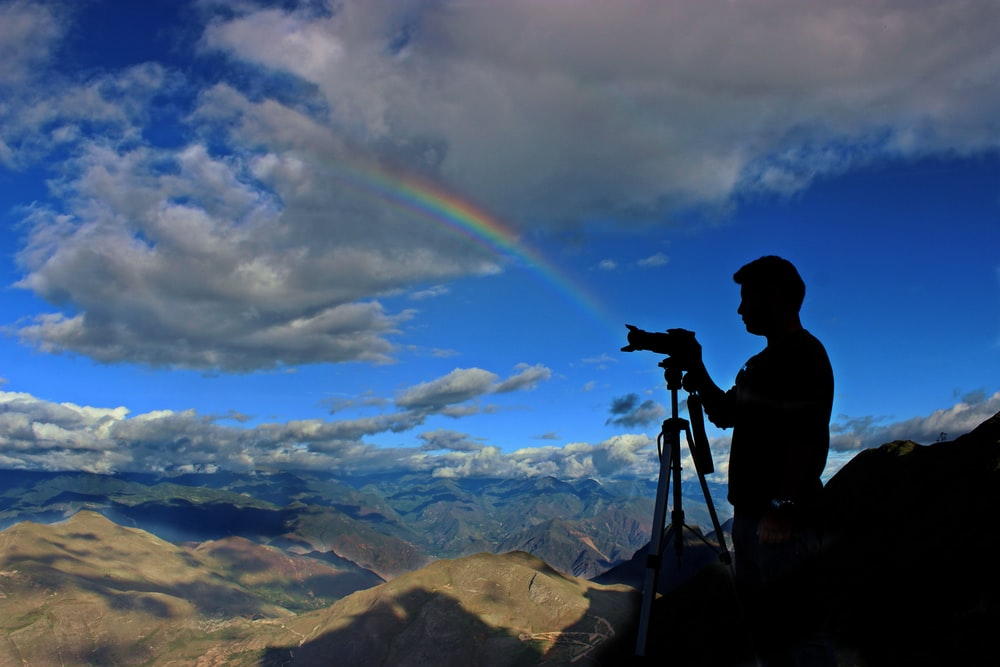 silhouette photo of holding camera with stand during daytime with rainbow