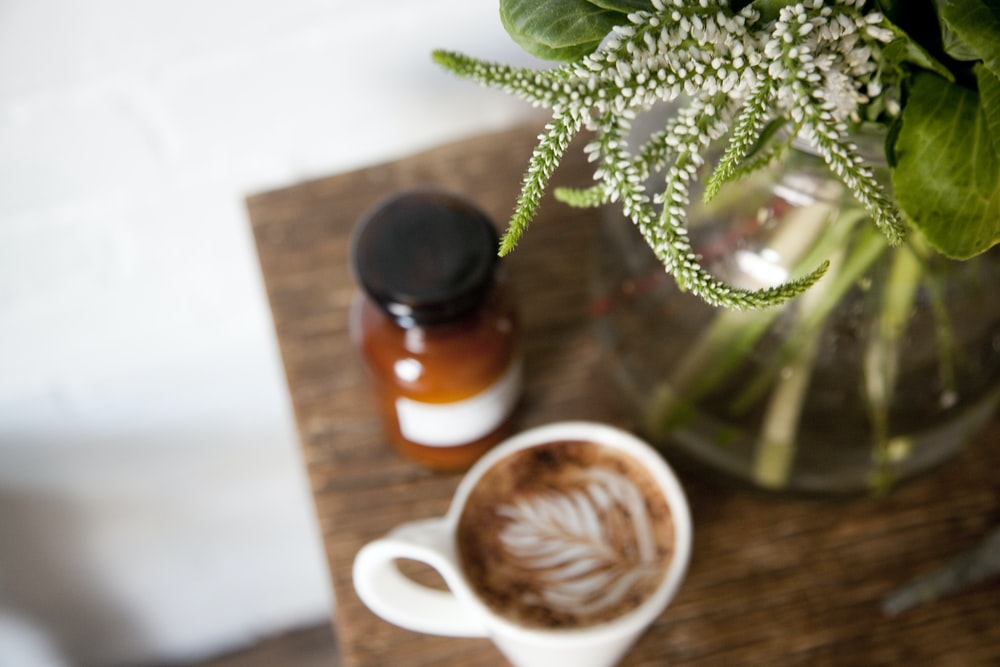 photo of white ceramic cup with coffee on table