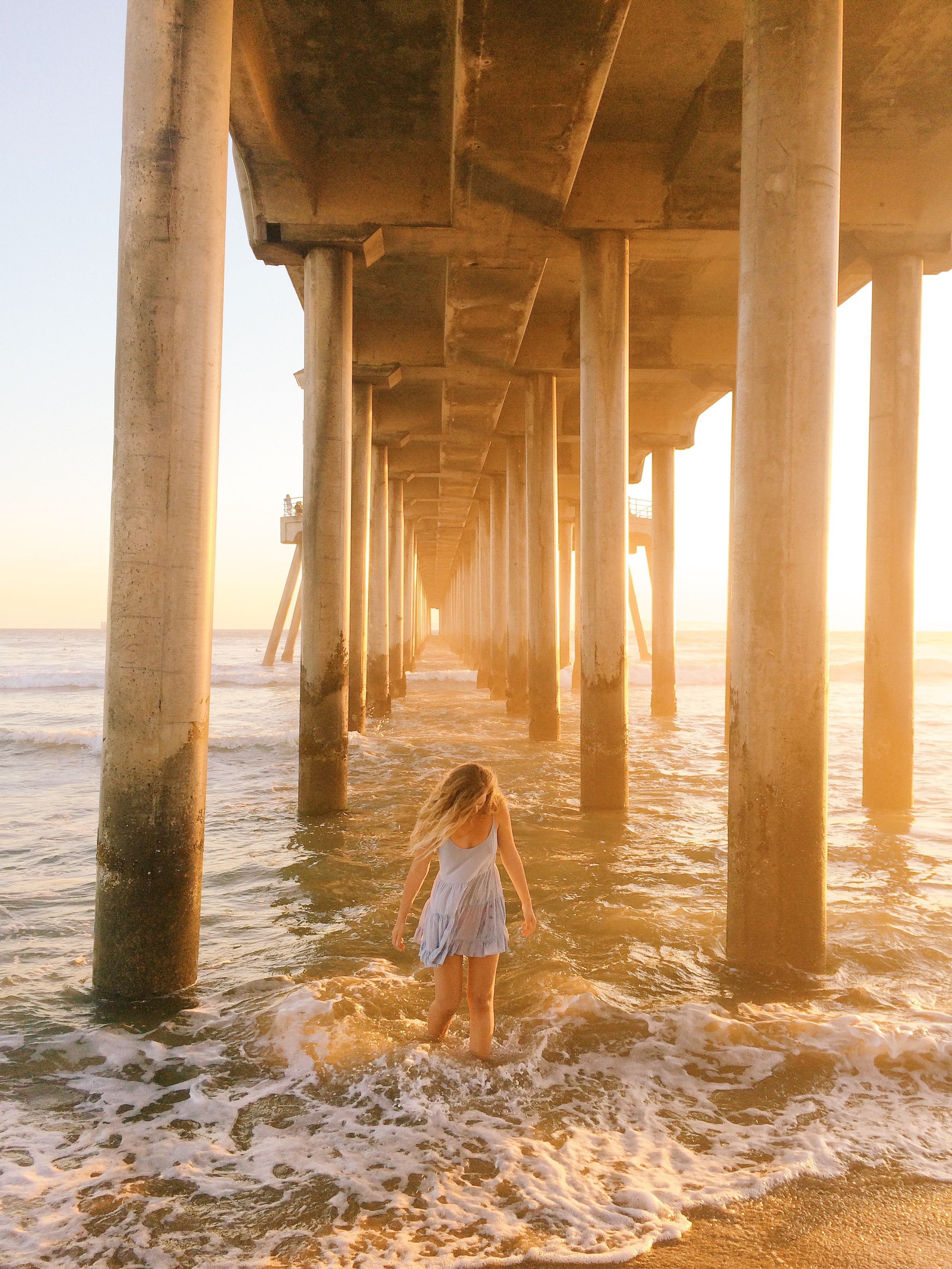 Woman in shallow water between pier pillars at Huntington Beach