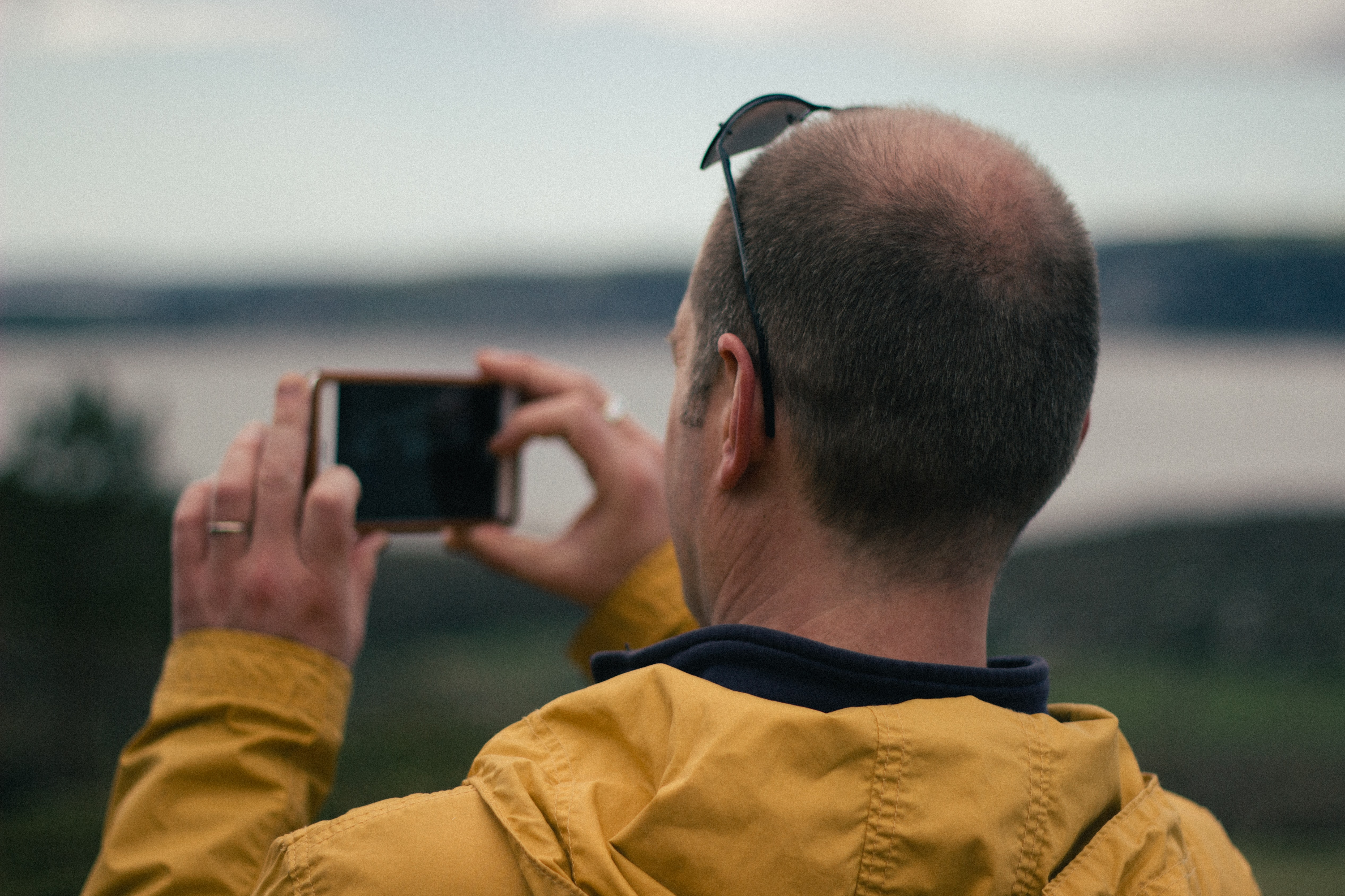 Man taking a picture of the landscape on is iphone