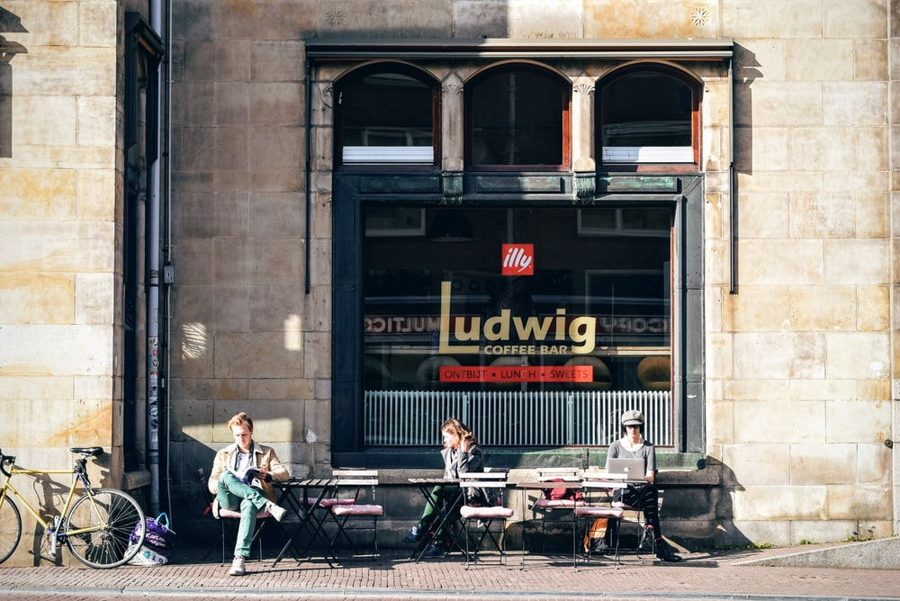 three person sitting on outdoor chair in front Ludwig cafe