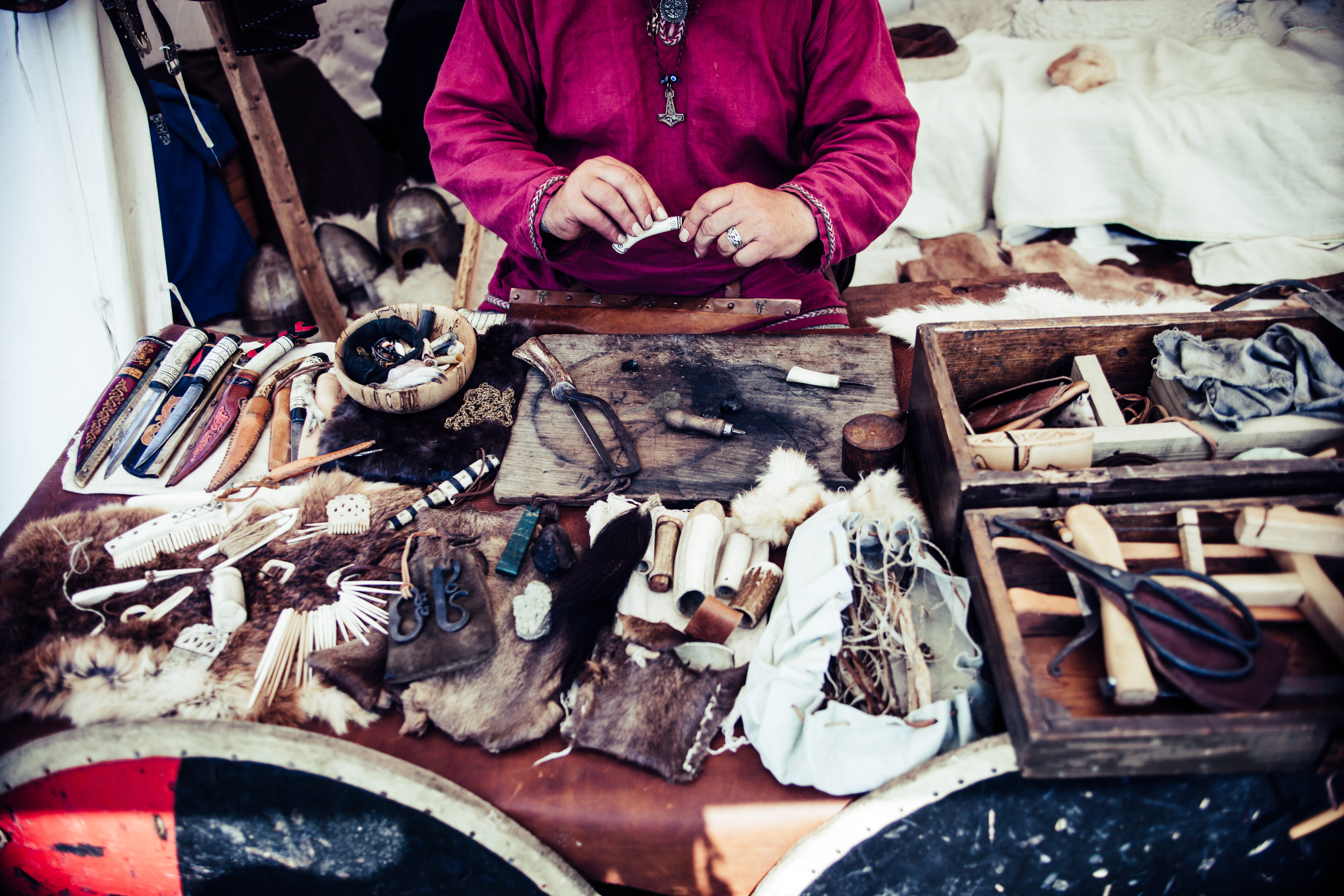 A person crafting various trinkets from leather and wood