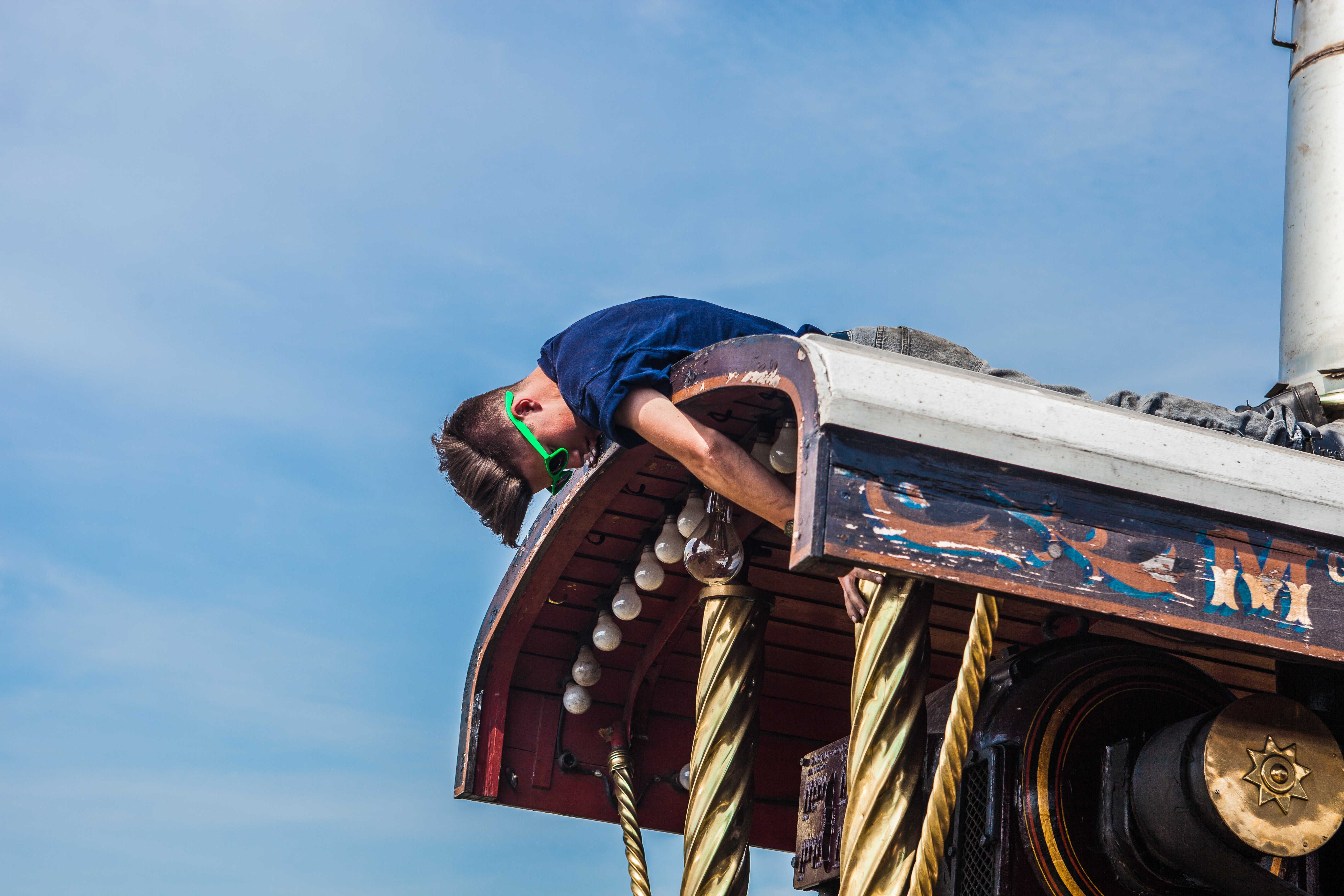 A man in sunglasses repairing a traction engine in a fairground