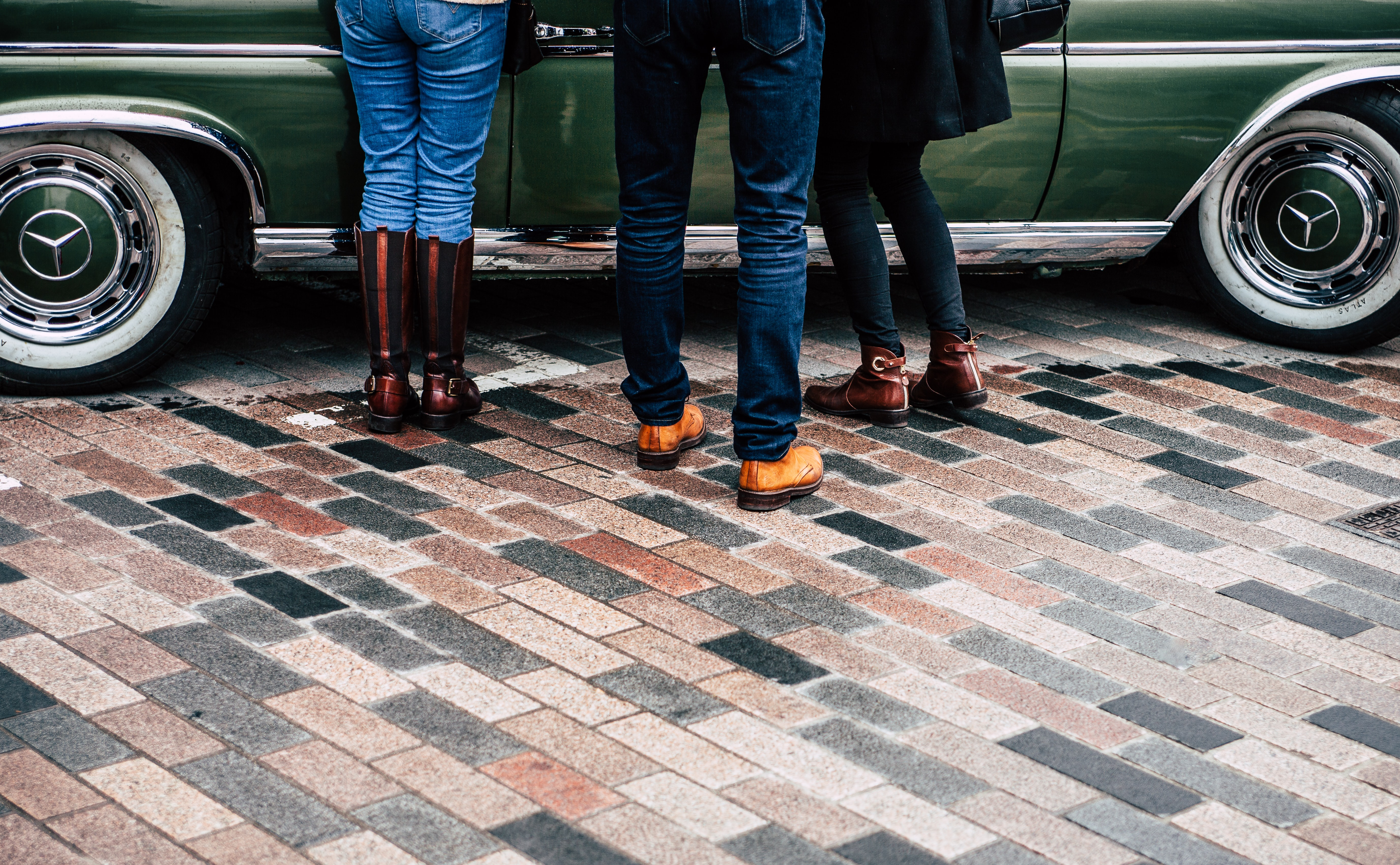 People standing on a brick road in front of a vintage Mercedes Benz car at Lewis Cubitt Park