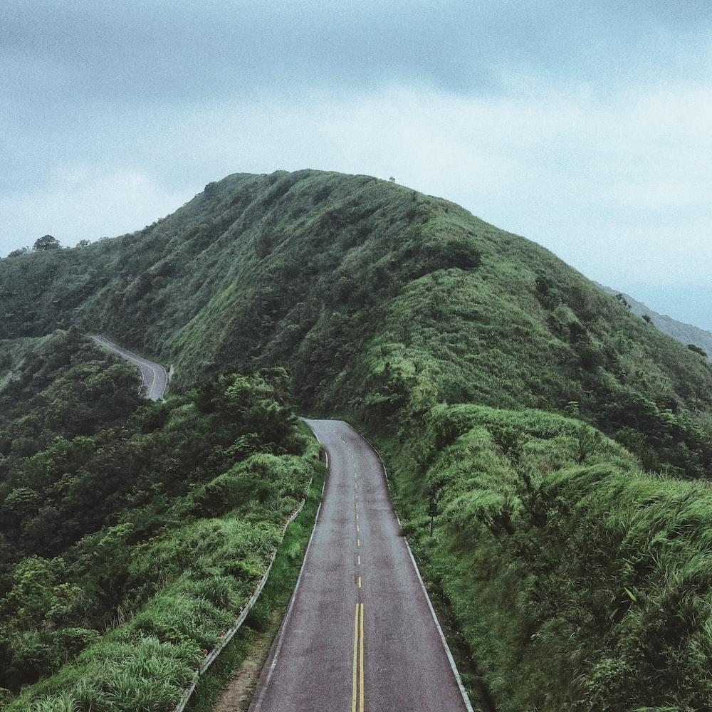 photo of road between mountain