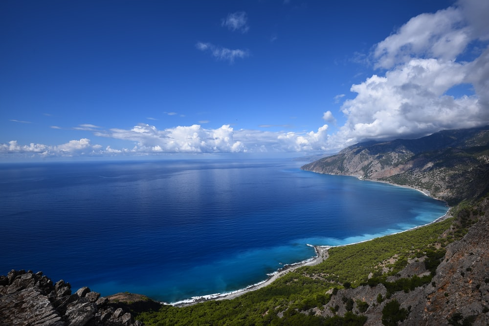 blue ocean water beside mountain under blue and white cloudy sky