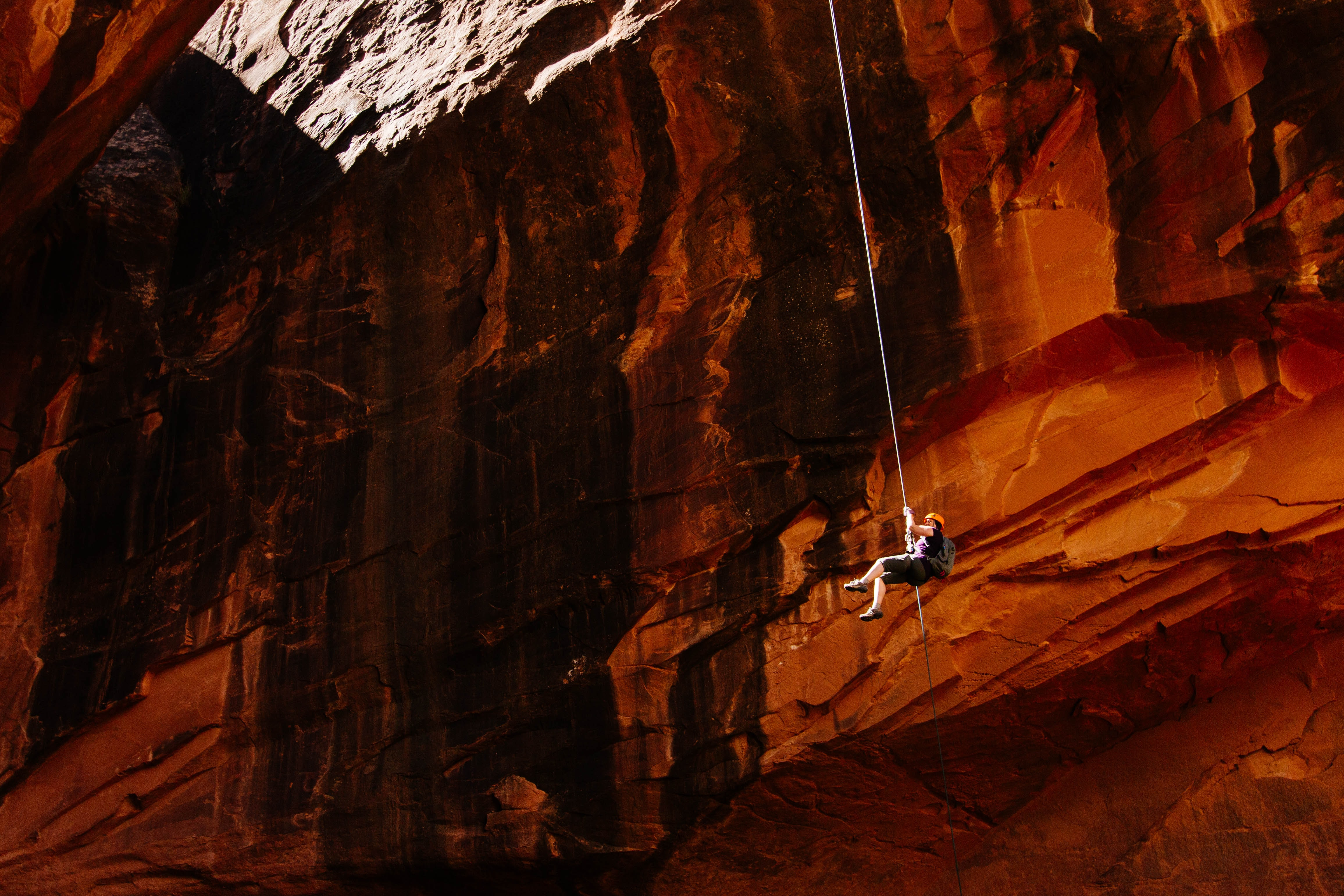 Climber belays down the steep side of a red mountain in Moab
