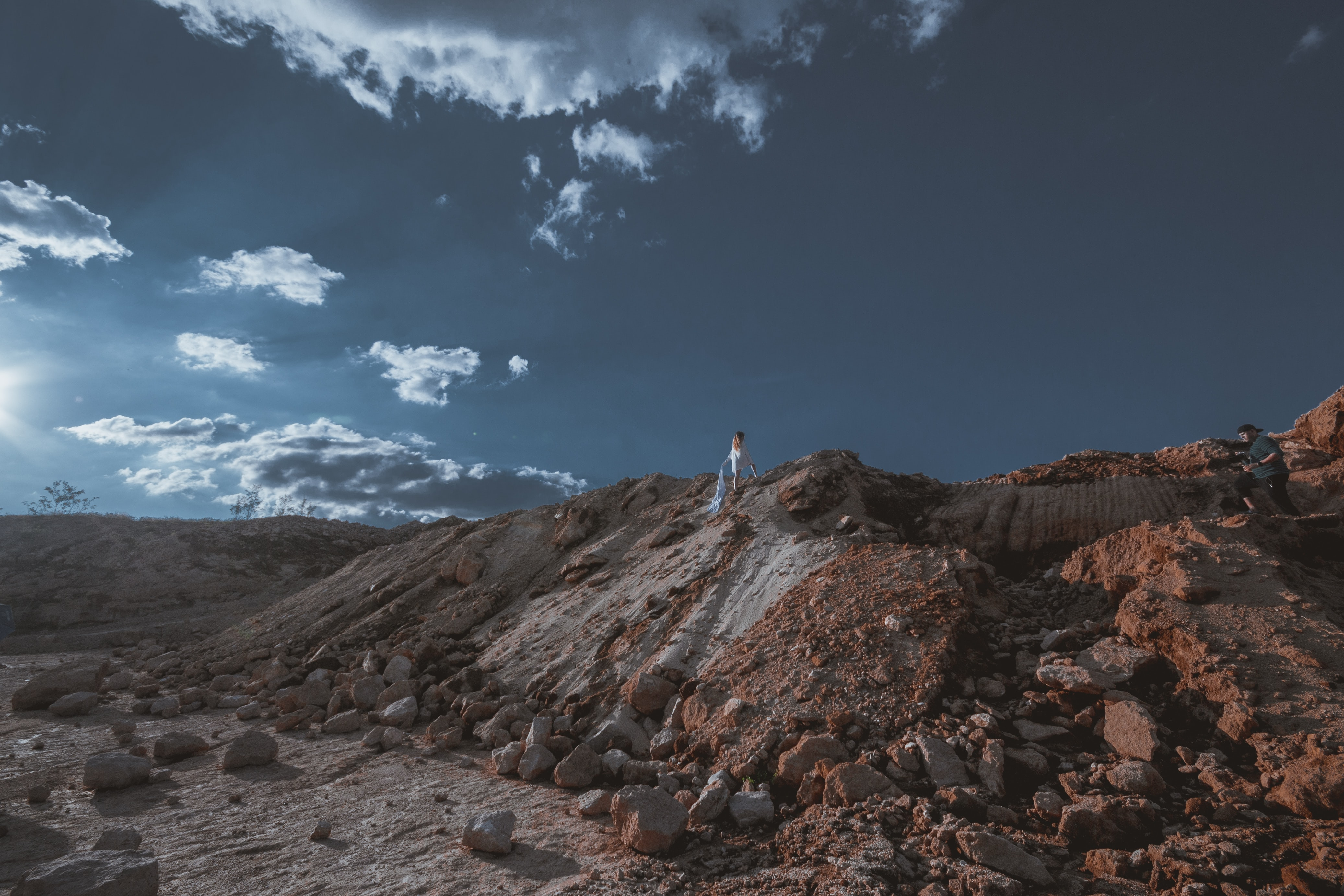 Person stands at the peak of a sandy mountain in the desert