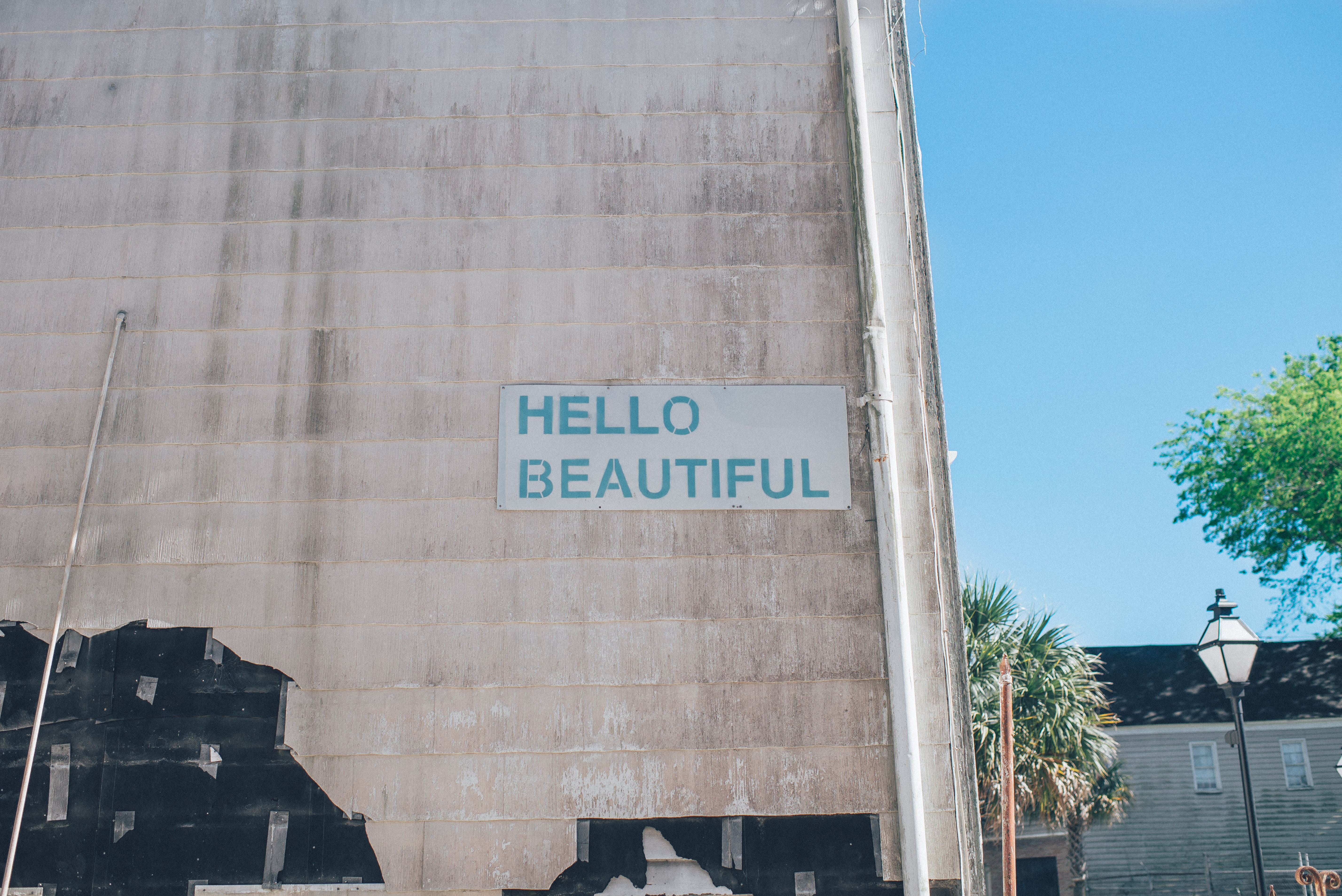 Green hello beautiful sign on urban wall with blue sky in background, Charleston
