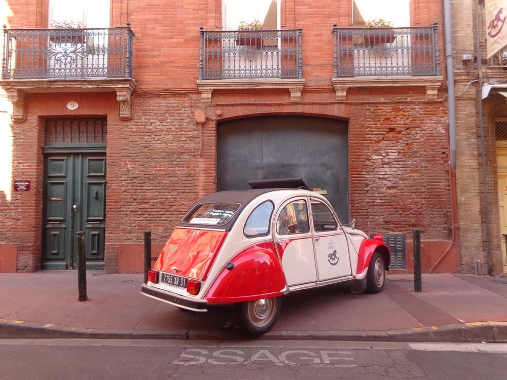white and red Volkswagen Beetle parked beside building during daytime