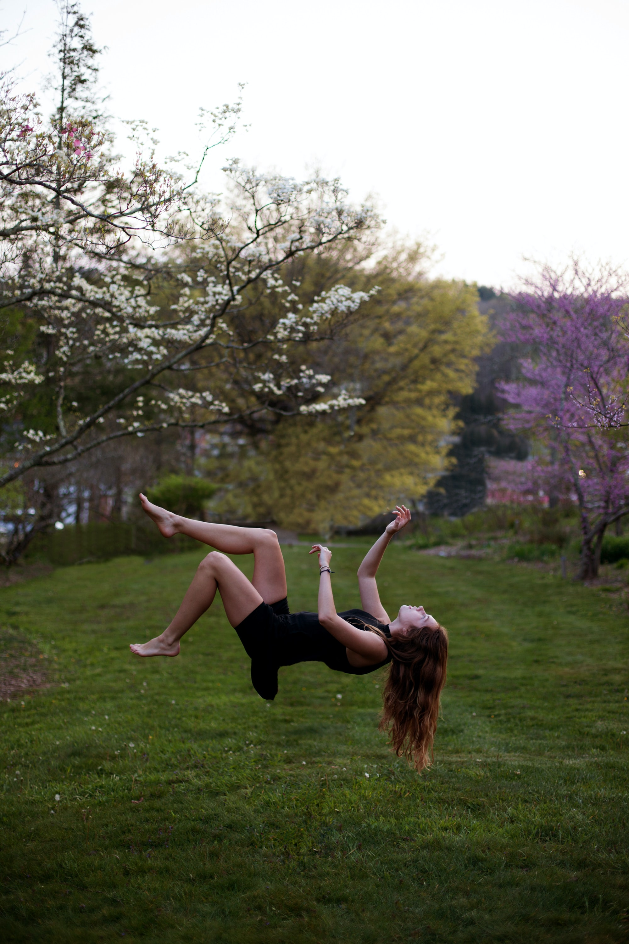 A person floating or falling on grass in a meadow in Boone