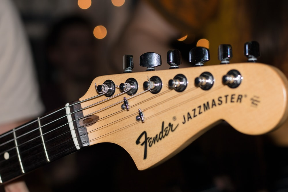 A close-up of the headstock of a Fender Jazzmaster guitar