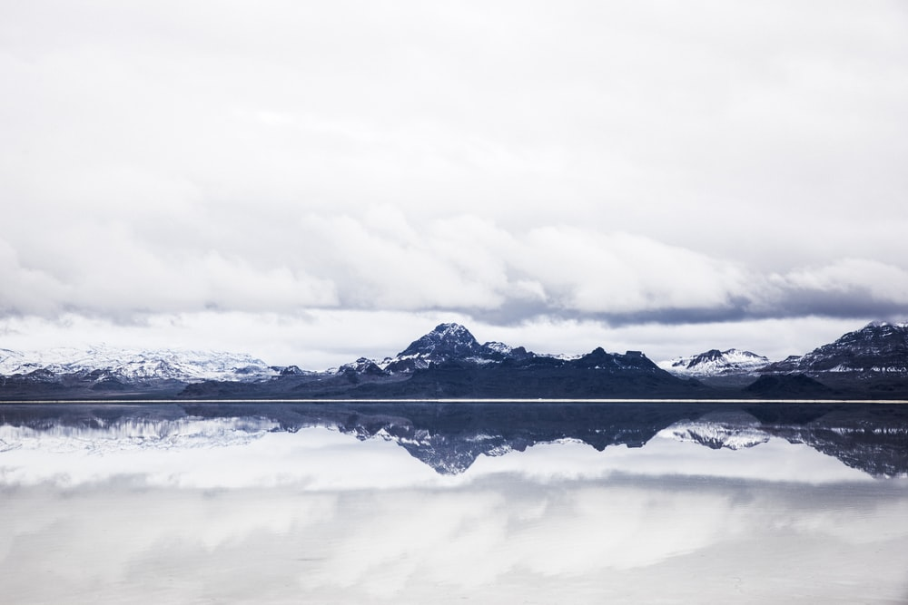 snow capped mountain under white clouds in mirror reflection photography