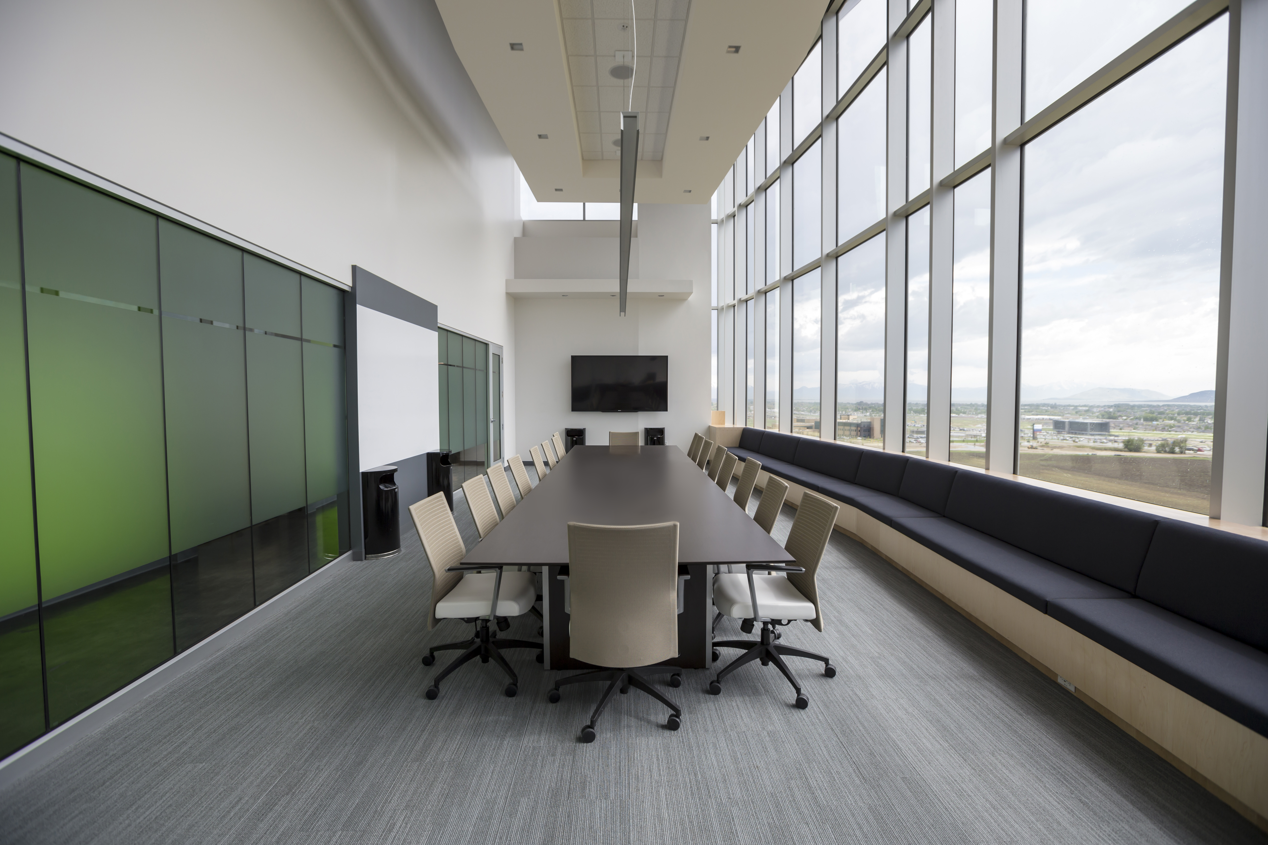 An empty elegant boardroom with a long table and tall windows