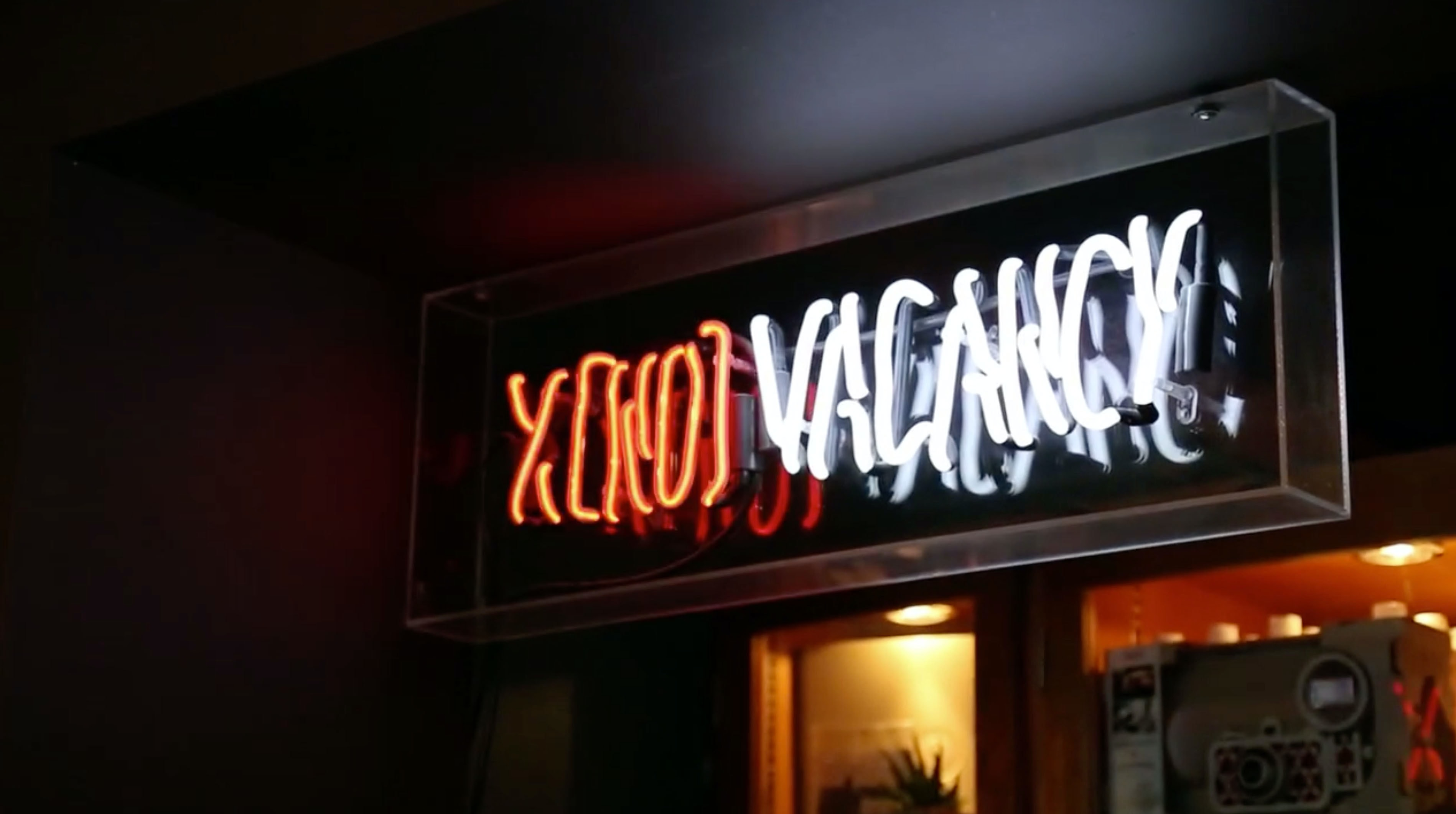 "Neon ""no vacancy"" sign lit up by an urban motel at night"