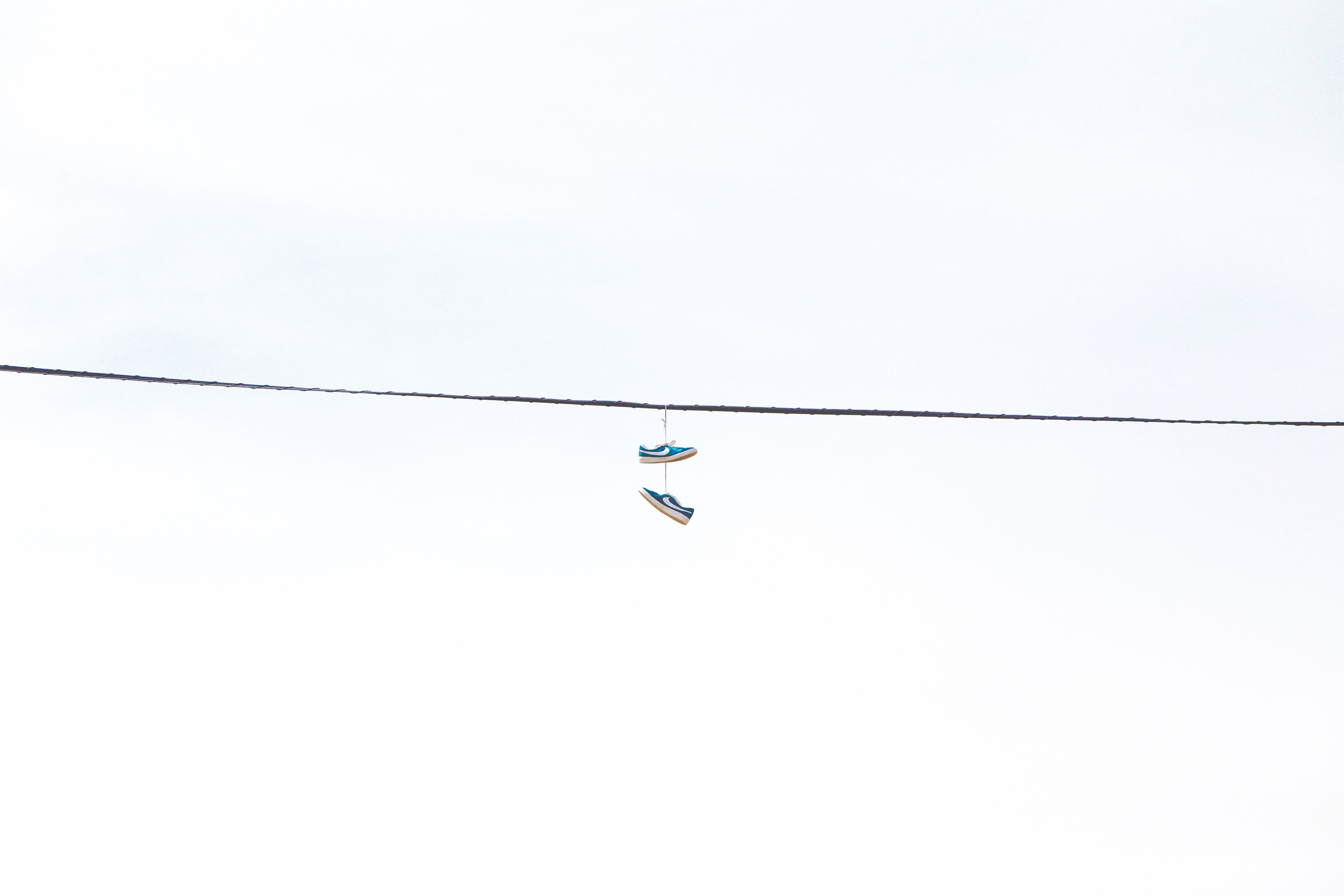 pair of green low-top sneakers hanged on wire