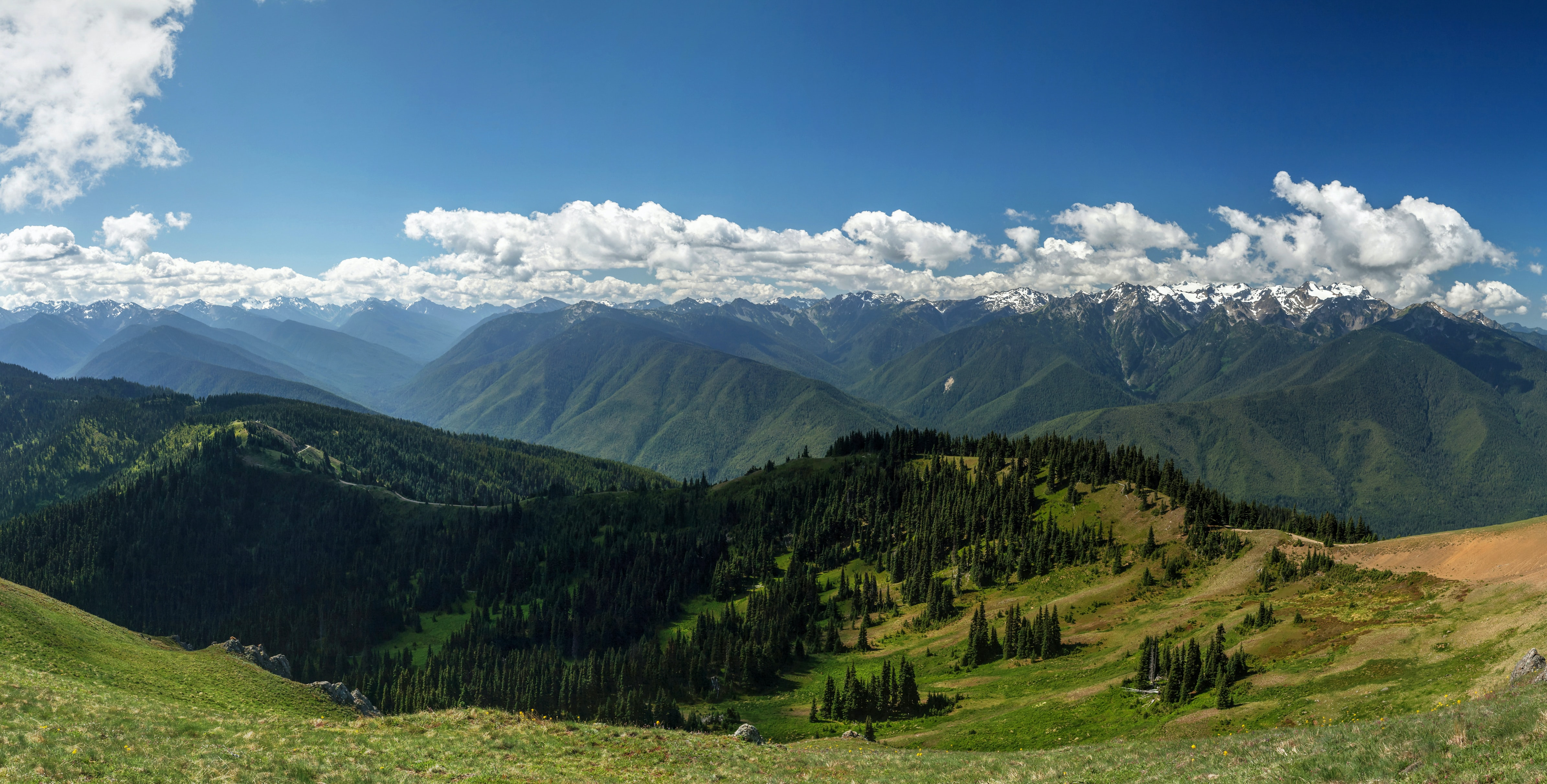 Green mountains with snow-topped crests under fluffy clouds