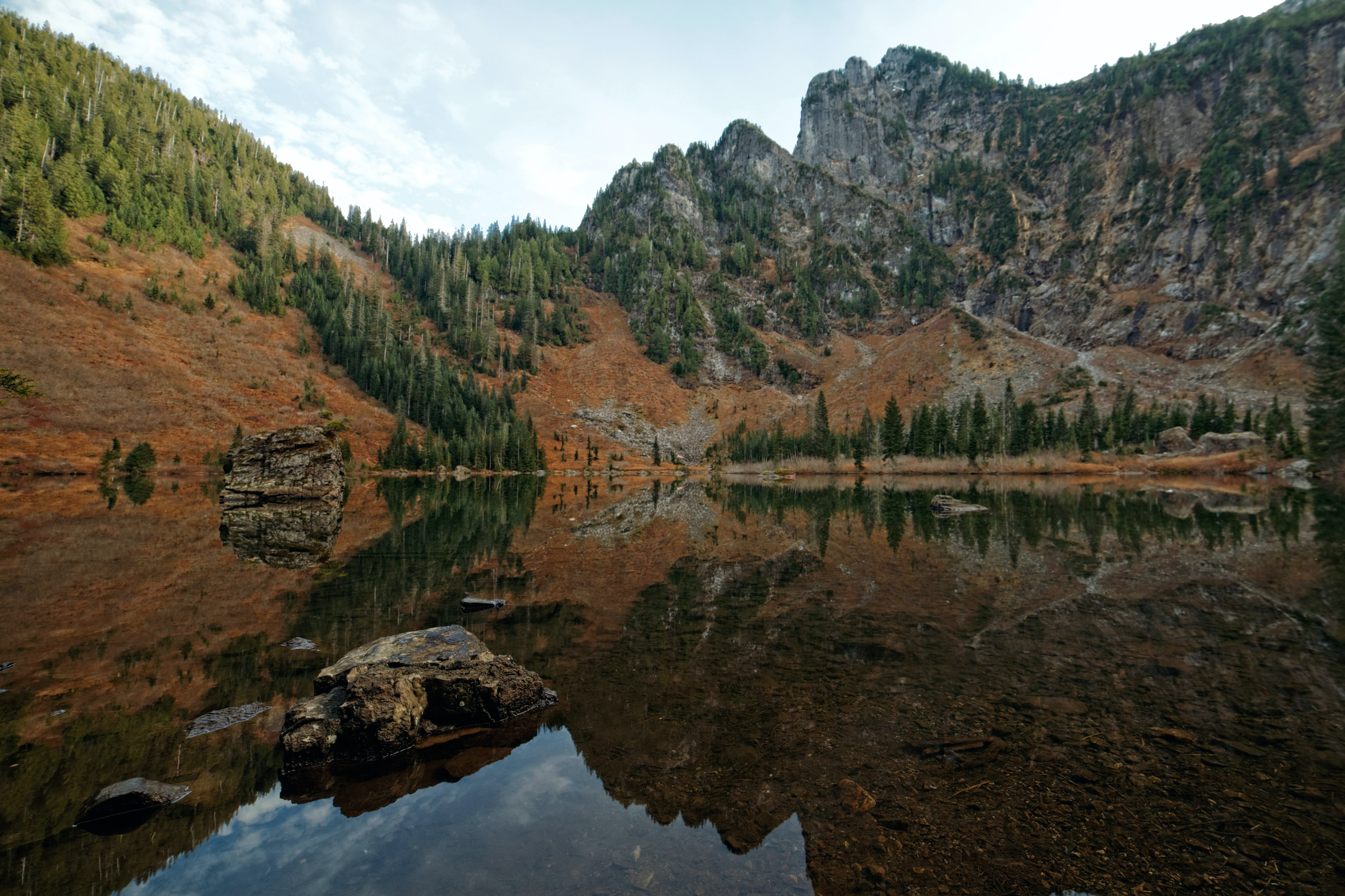 A wooded cliff reflected in Heather Lake