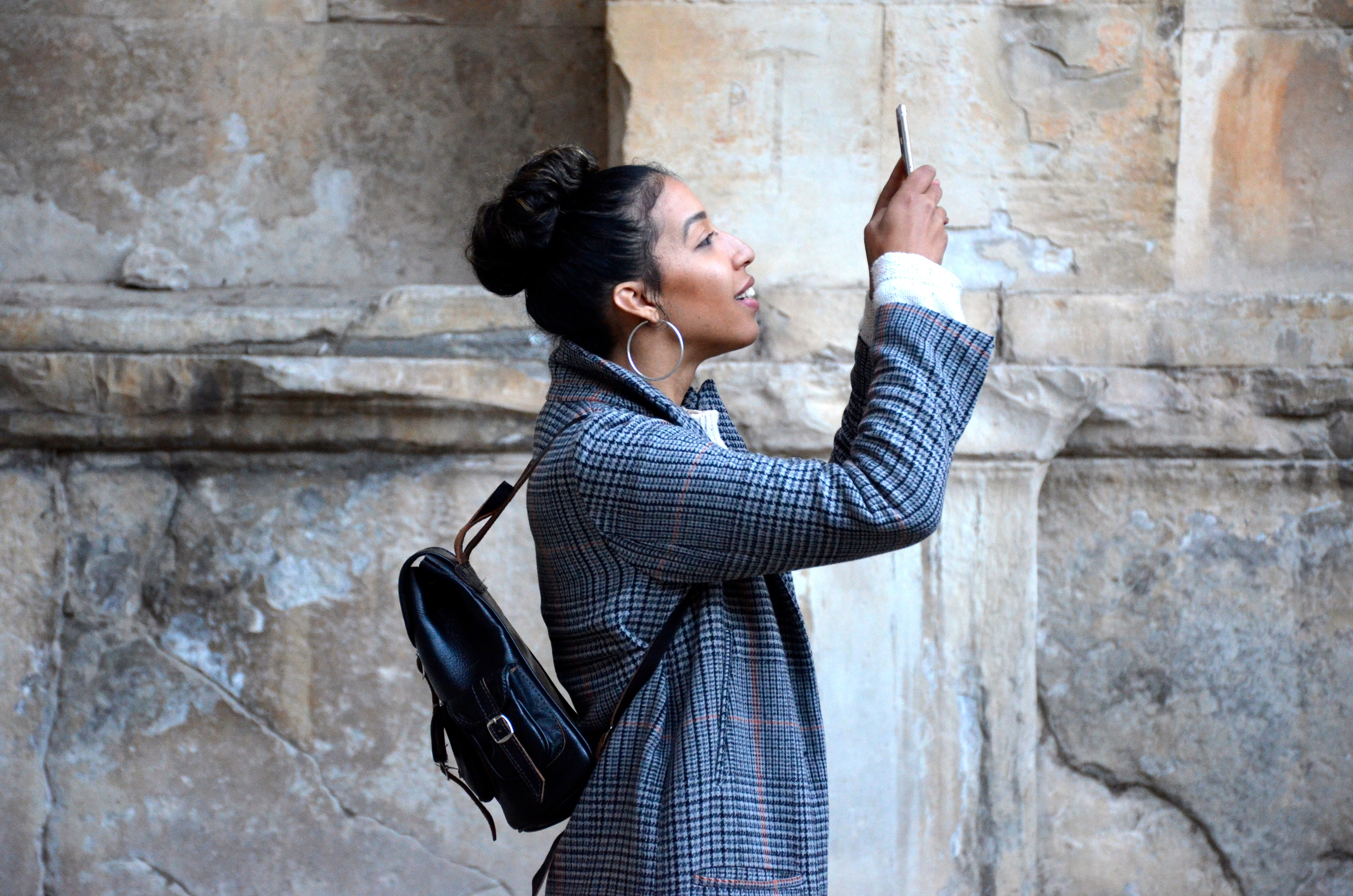 A female tourist smiling while taking a photograph with a smartphone