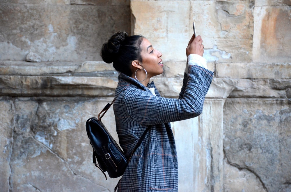 woman wearing blue shirt while looking at her phone