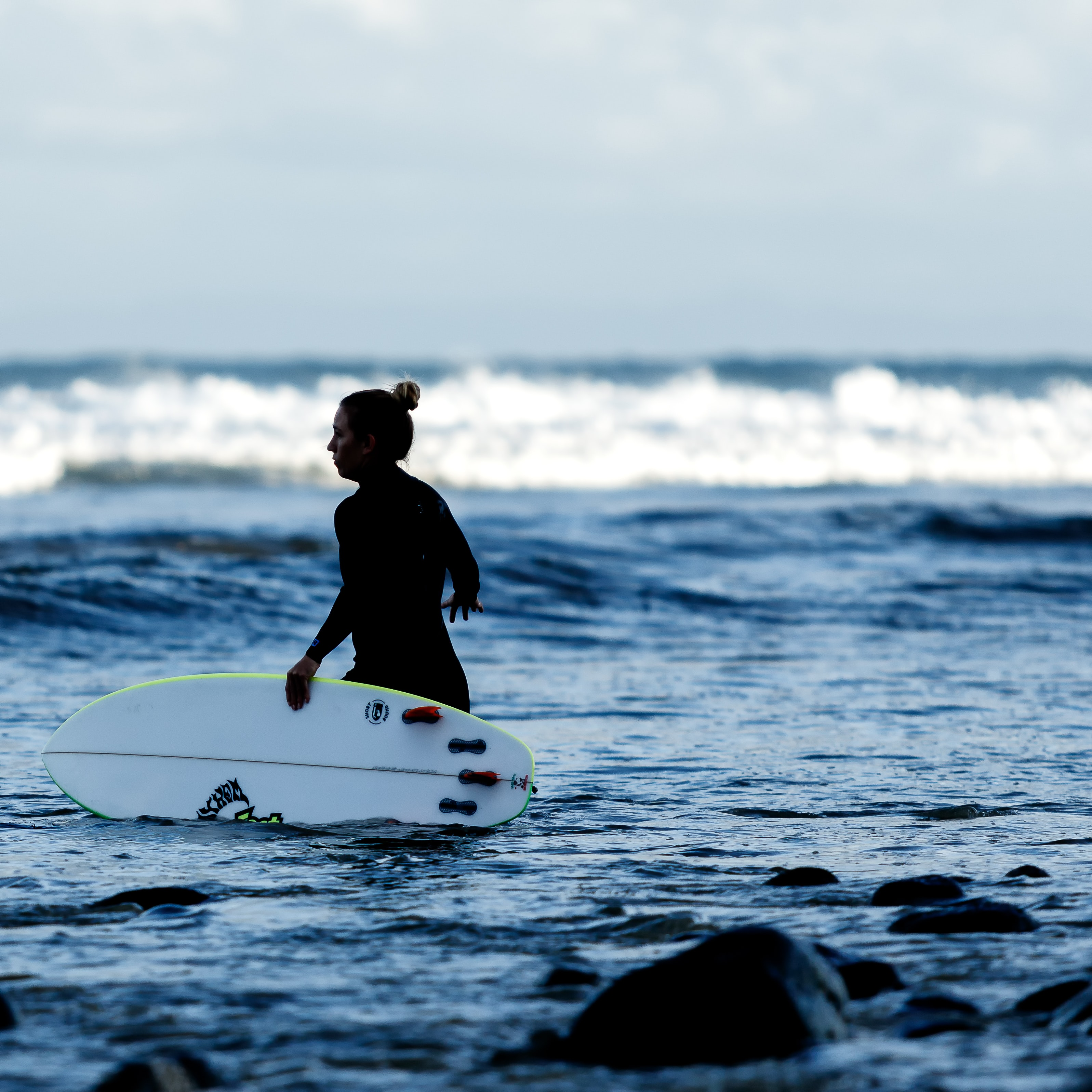 woman holding white surfboard on body of water