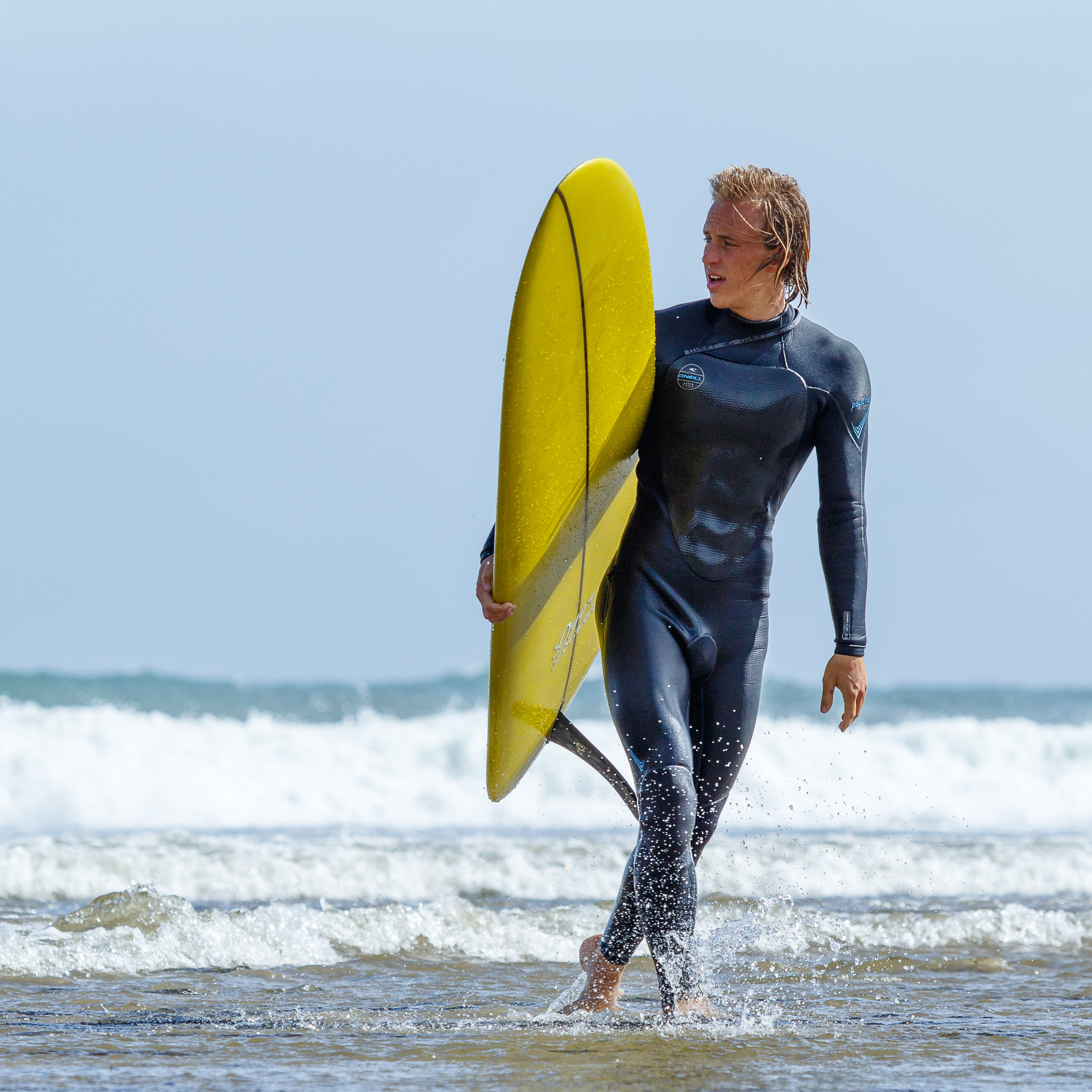 A male surfer with blonde hair, wearing a black wetsuit, carrying a yellow surfboard in the shallow sea water at Malibu