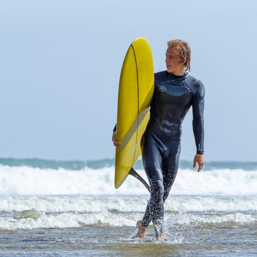 man holding yellow surfboard