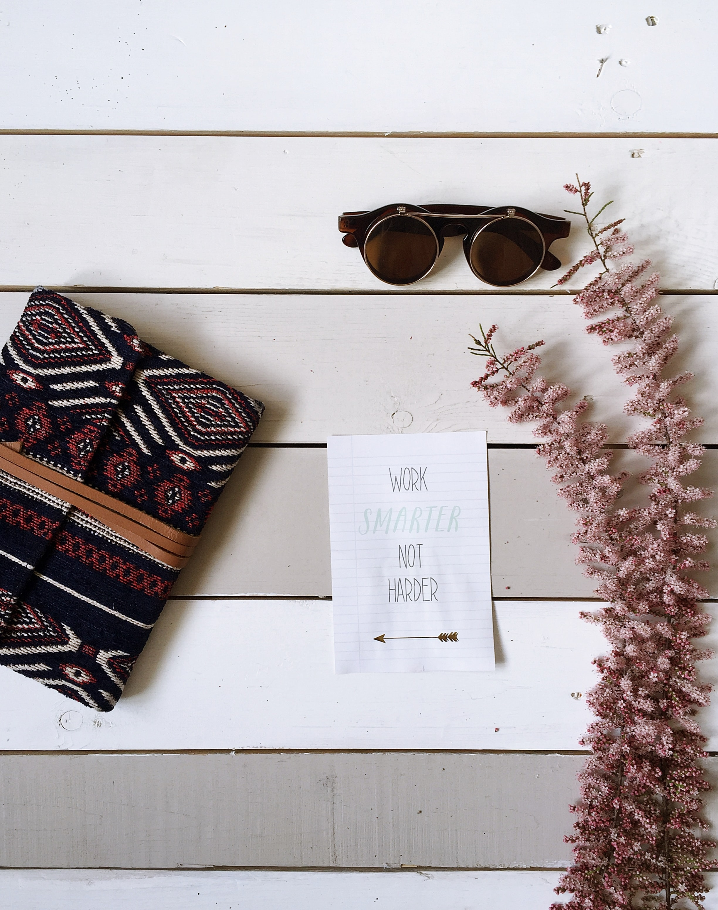 "A flatlay image of flowers, a notebook, a piece of paper that says ""Work smarter not harder,"" and a pair of glasses."