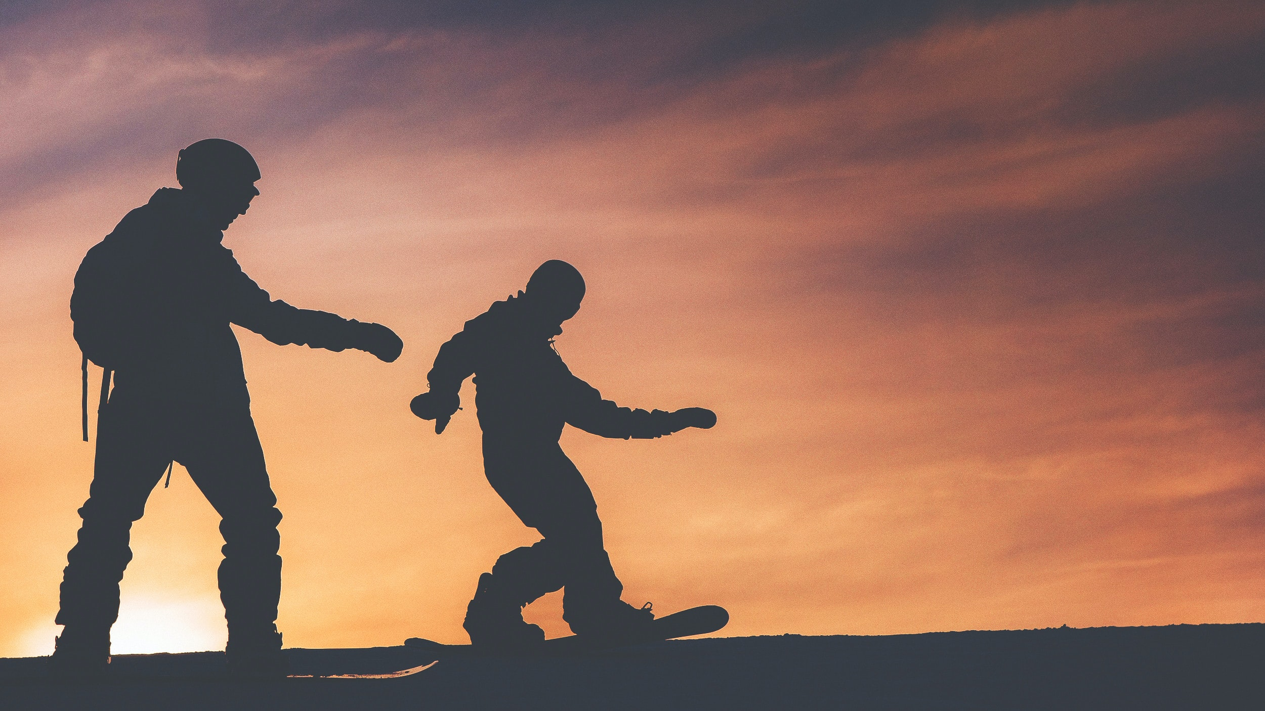 silhouette photo of two person riding on snowboard