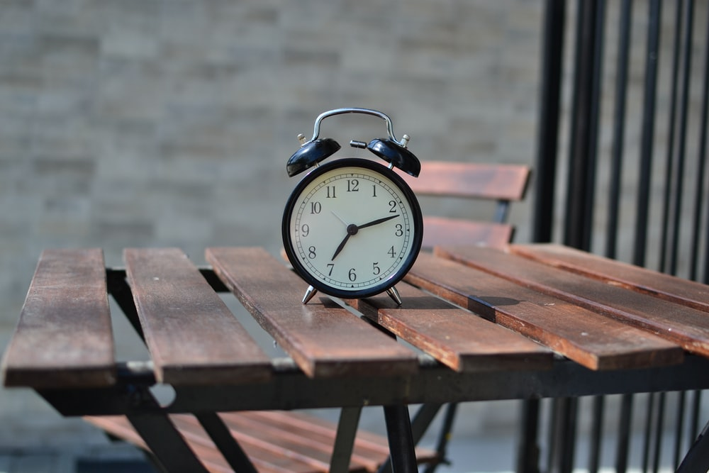 black steel alarm clock on top of brown table