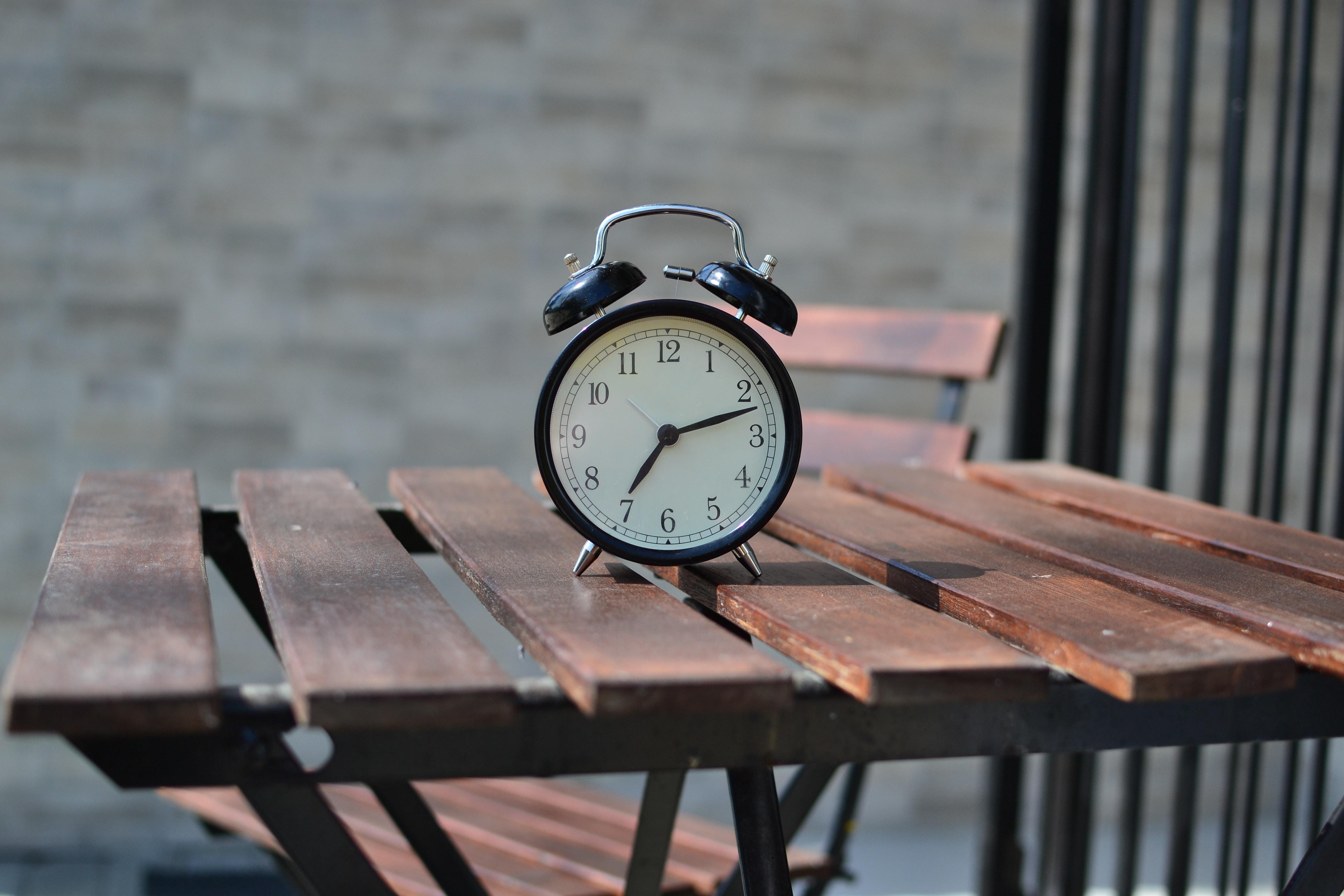 A black alarm clock on a chair