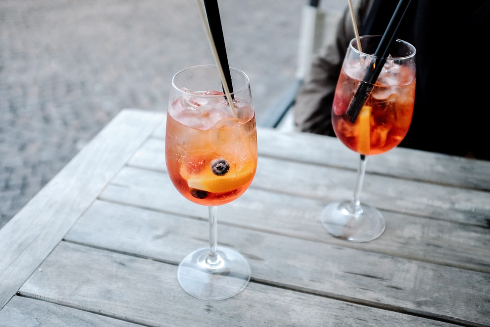 Cold cocktail alcoholic wine drinks in glass with straw on a table in Anzio
