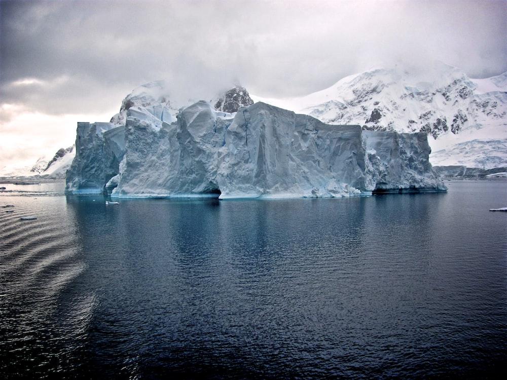 white iceberg near white mountains