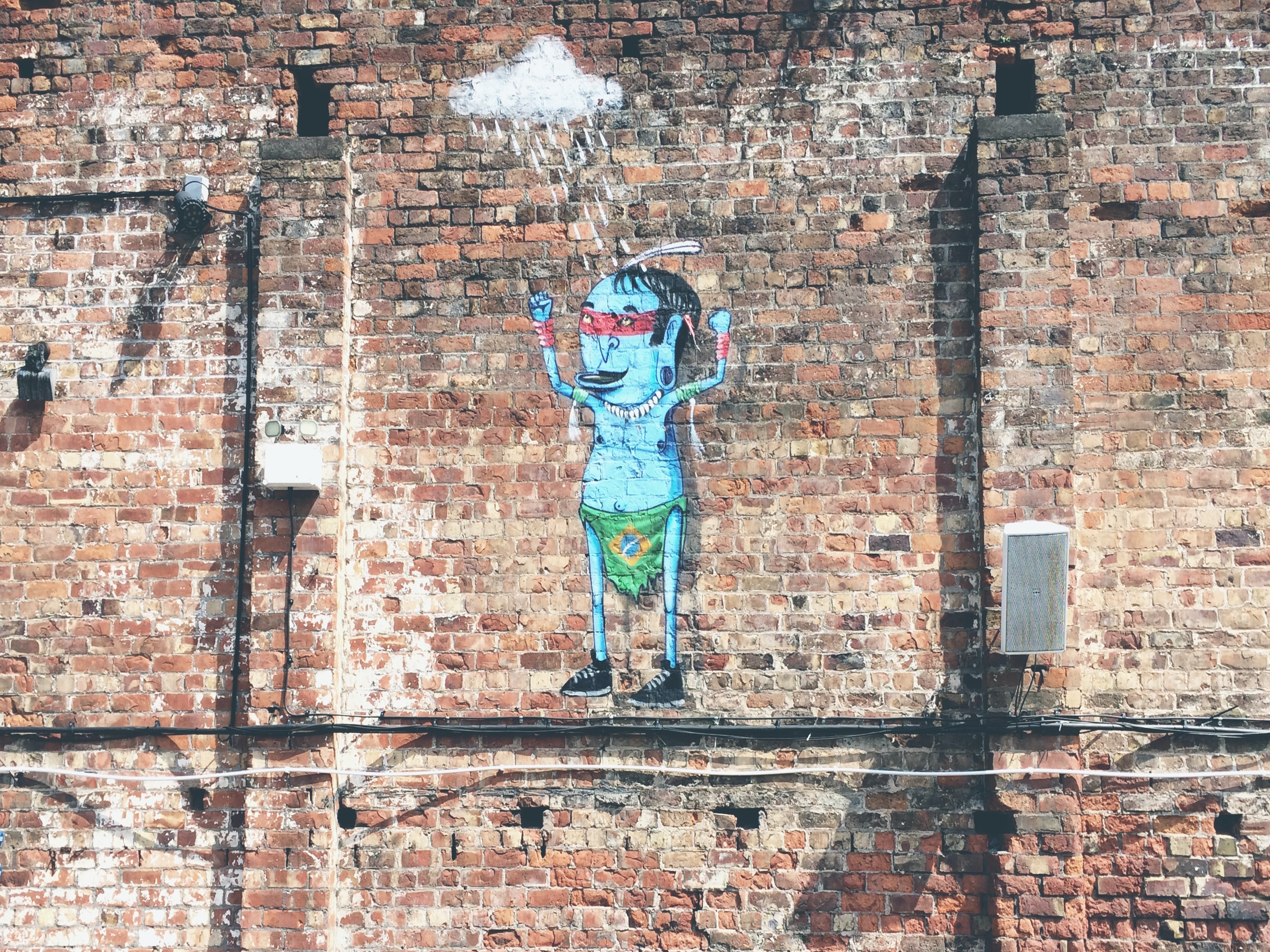 Random cartoon art piece on plain brick wall in Liverpool